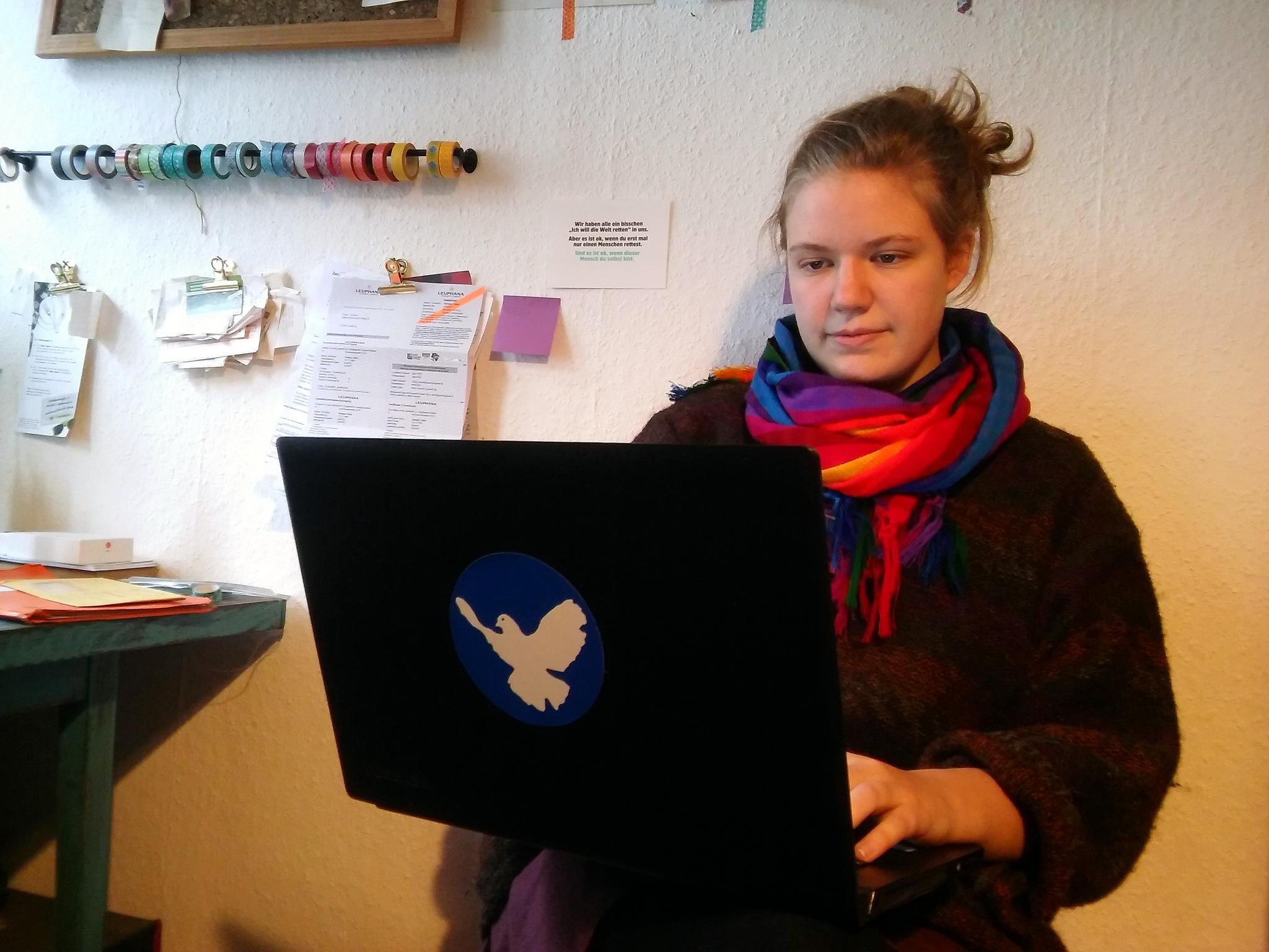 Eine junge Frau mit hellem Gesicht und zurückgebundenen Haaren sitzt entspannt an eine Wand gelehnt und schaut auf den Bildschirm des aufgeklappten Laptops auf ihren Knien. Der Laptop-Deckel ist mit einer Friedenstaube beklebt.