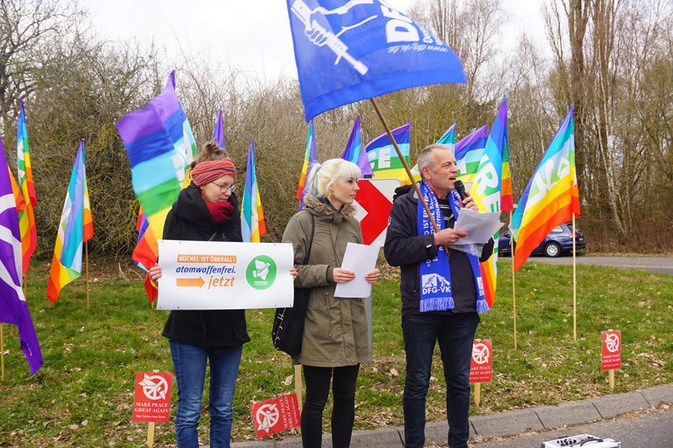 Zwei Frauen und ein Mann stehen winterlich gekleidet nebeneinander; im Hintergrund zahlreiche bunt gestreifte Friedensfahnen und die blauweiße Fahne der DFG-VK.