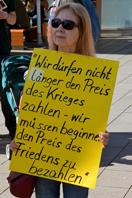 Eine Frau mit schulterlangen Haaren und dunkler Sonnenbrille trägt ein großes gelbes Pappschild mit der genannten Schrift vor ihrer Brust.