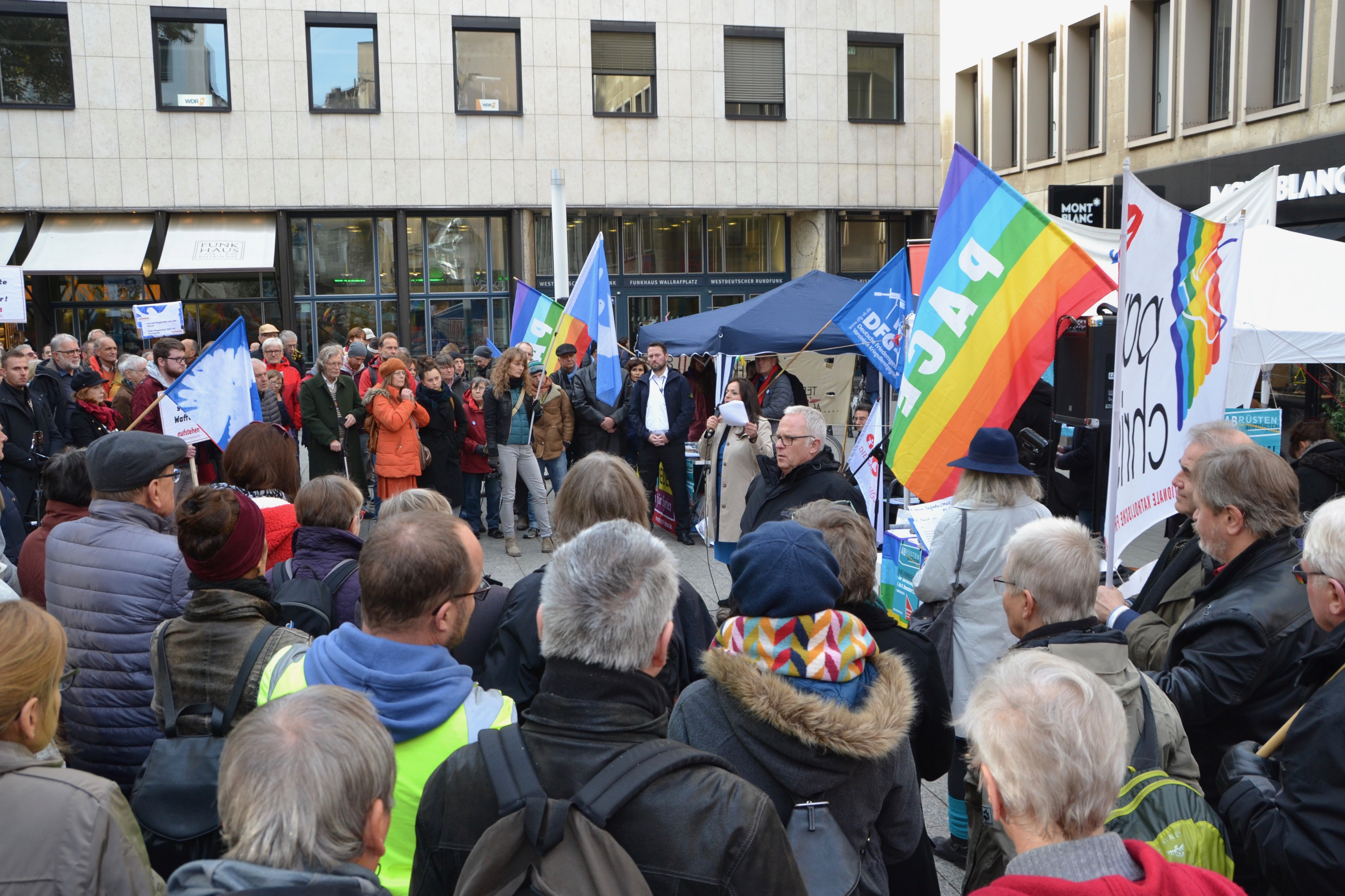 Ein dicht gedrängter Kreis von Menschen, die einer Rednerin zuhören. Friedensfahnen und Transparente im Hintergrund.