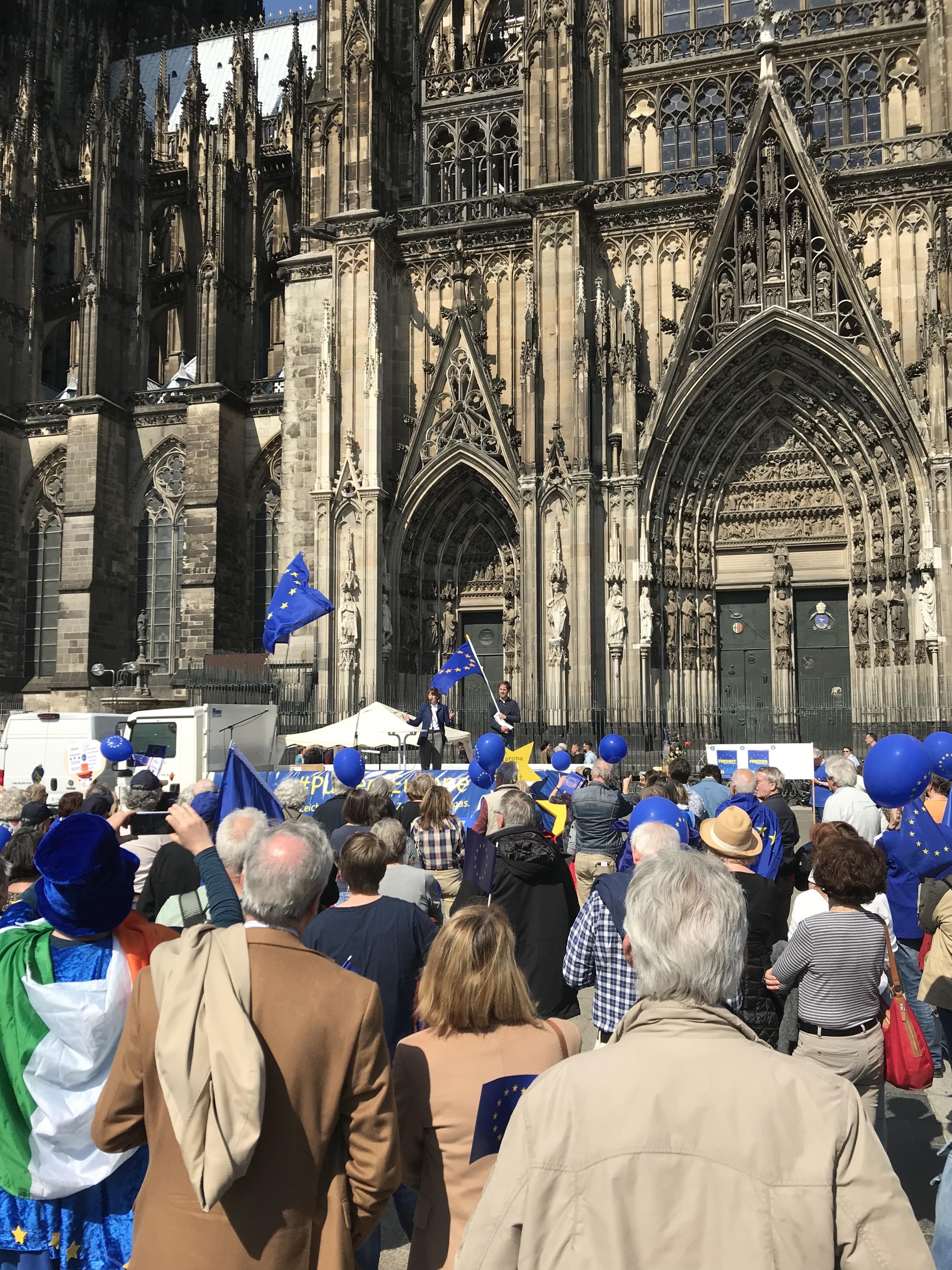 Eine Menge mit blauen EU-Flaggen schaut bei strahlendem Sonnenschein Richtung Bühne, welche mit dem Rücken am Seitenportal des Kölner Doms steht. Auf der Bühne aus der Ferne winzig die Oberbürgermeisterin.