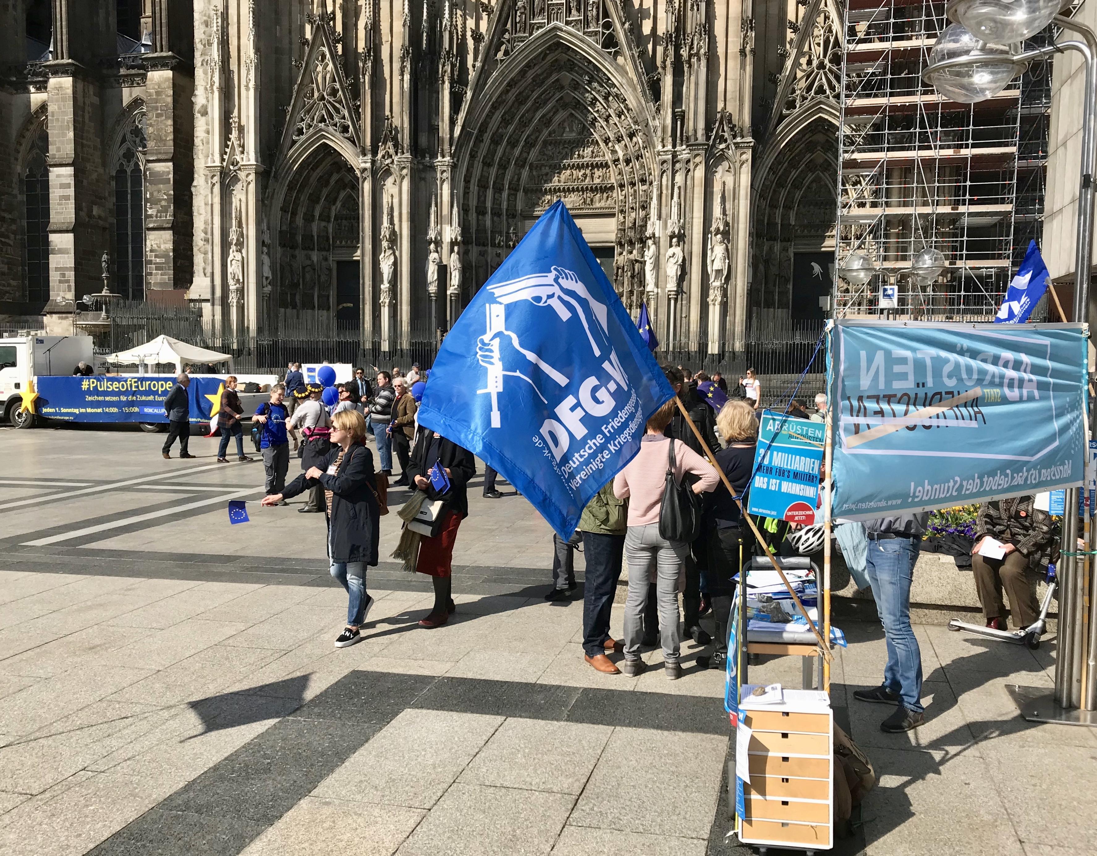 Ein kleiner Infotisch mit Transparenten und der DFG-VK-Flagge. Dahinter die Bühne von Pulse of Europe und das Seitenportal des Kölner Doms.
