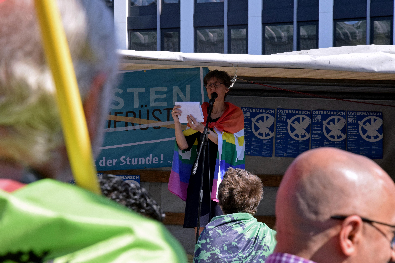 """Im Vordergrund stehen Leute, die einer Frau mit über die Schultern gehängter Friedensfahne zuhören. Sie steht im Schatten auf einer LKW-Bühne. Hinter ihr sind Plakate """"Abrüsten"""" zu sehen."""