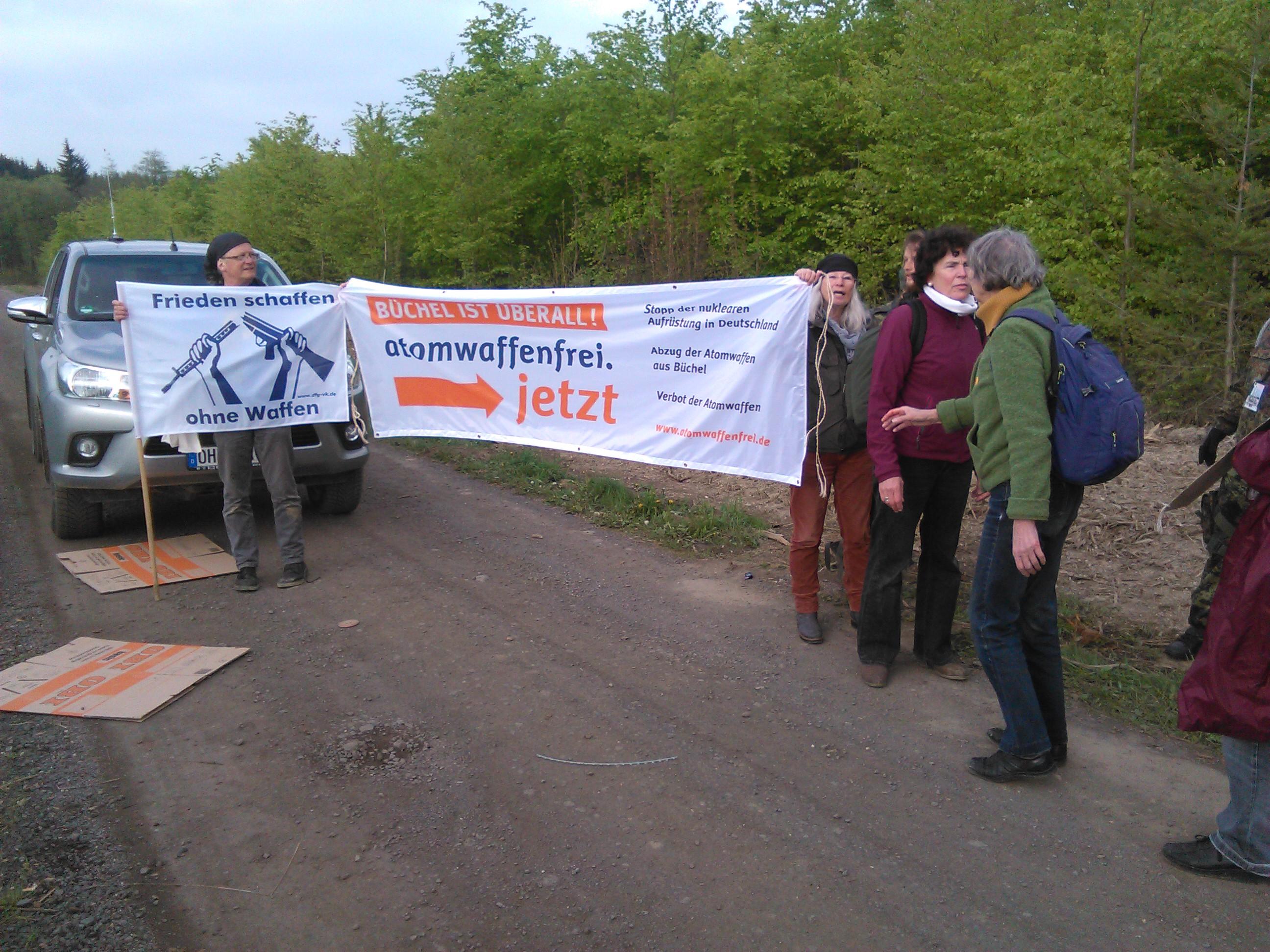 """Eine Gruppe hält auf einer Fahrpiste Transparente """"Frieden schaffen ohne Waffen"""" und """"Büchel ist überall - Atomwaffenfrei jetzt!"""". Ganz rechts im Bild steht ein Soldat, der nicht ganz zu sehen ist."""