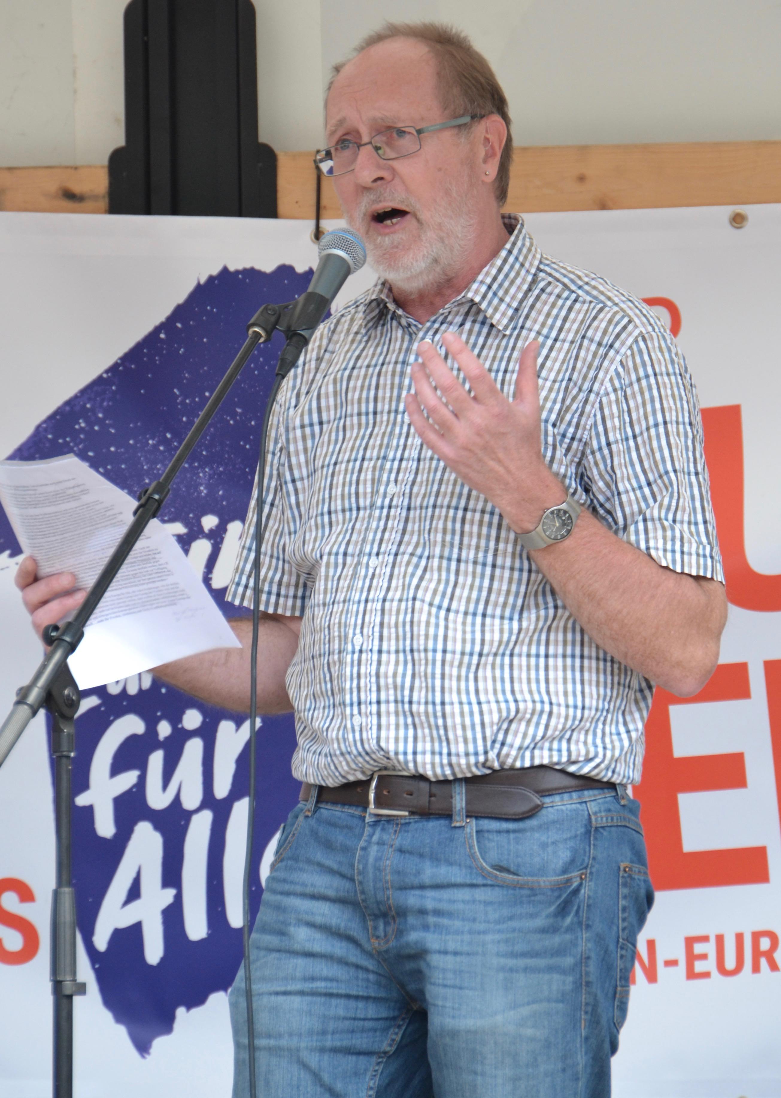 Ein älterer Herr mit kurzrasierten schütteren grauen Haaren in einem hellen Sommerhemd und Jeans spricht in ein Mikro.
