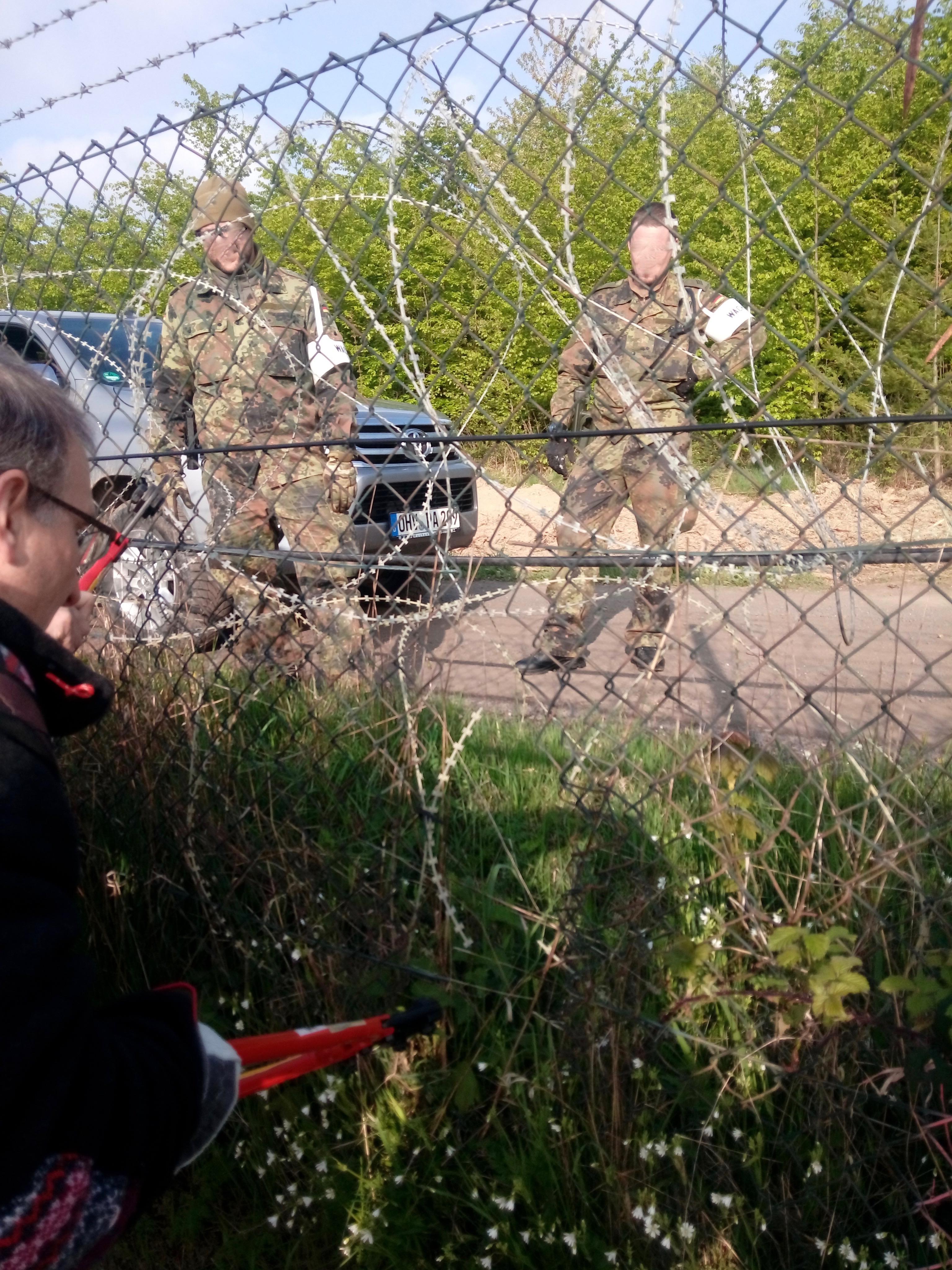 Im Vordergrund knipst ein Mann mit Brille mit einem Bolzenschneider einen Drahtzahn durch, hinter dem eine Rolle NATO-Stacheldraht liegt. Dahinter zwei uniformierte Militärpolizisten neben ihrem PKW. Sie schauen zu.