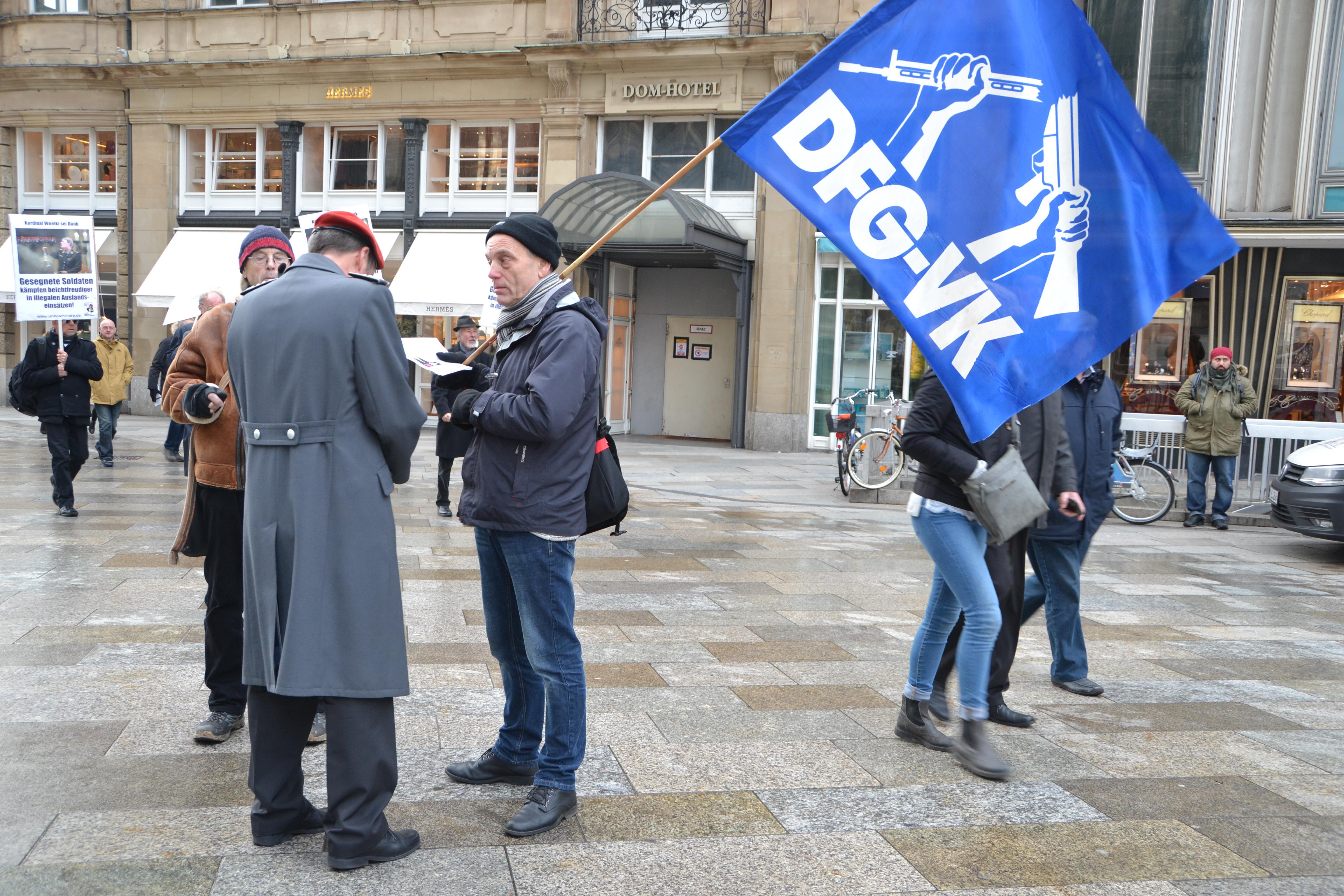 Ein älterer Mann mit dunkler Mütze und einer blau-weißen DFG-VK-Fahne mit dem zerbrochenen Gewehr in der Hand spricht mit einem Soldaten in einem langen grauen Mantel und einer weißroten Mütze.