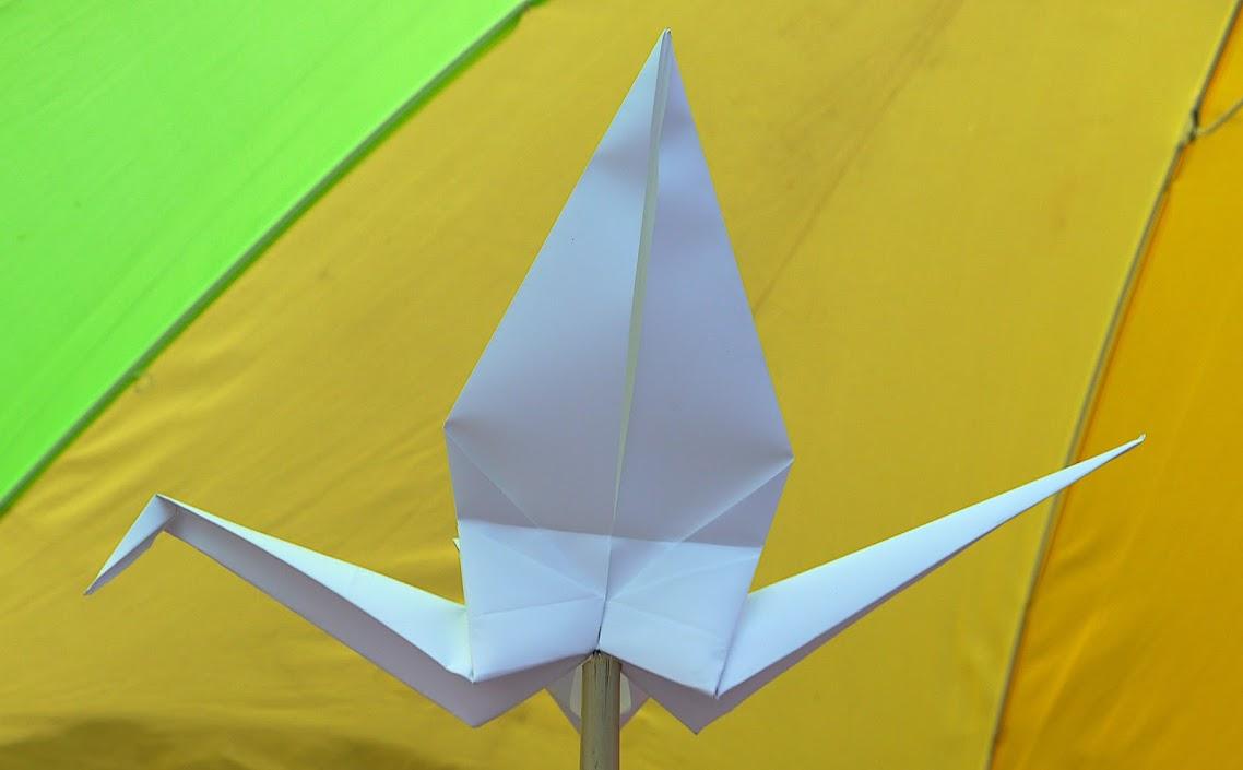 Ein weißer Papierkranich vor gelb-grünem Hintergrund.