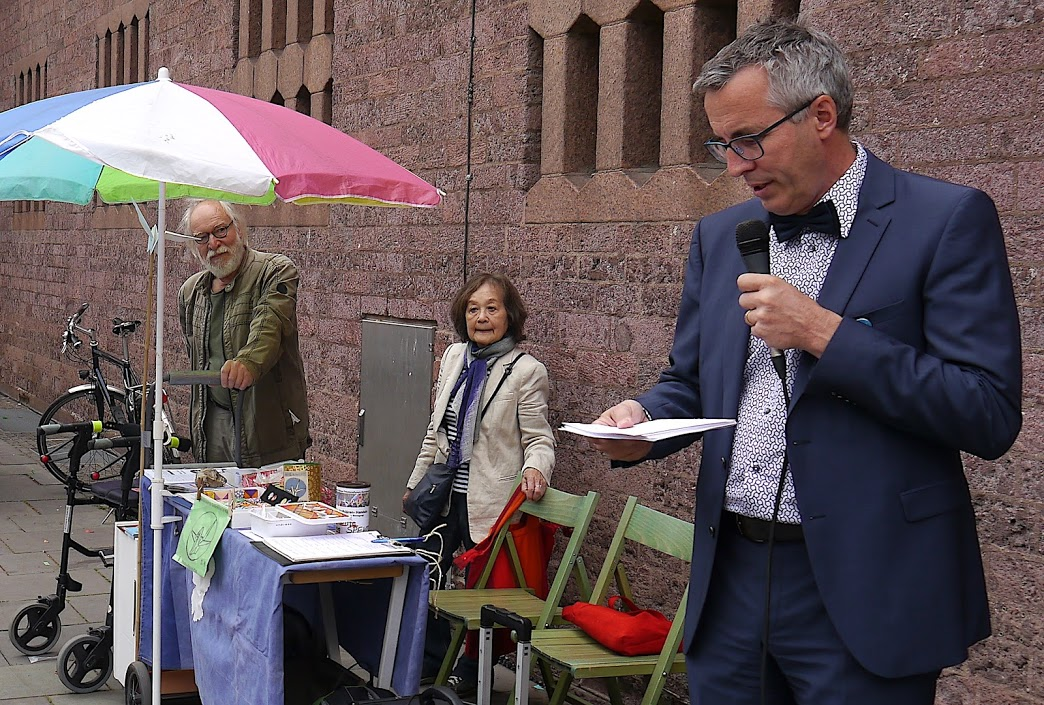 Ein schlanker Mann mit Brille und graumelierten Haaren spricht in ein Mikro. Er trägt einen blauen Anzug und Fliege. Links von ihm hören eine kleine asiatisch aussehende Dame und ein älterer Herr mit weißem Bart zu. Sie stehen an einem kleinen Tisch mit Infomaterial und grünen Holzstühlen.