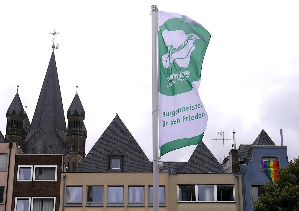 Im Hintergrund der grün-weißen Flagge sind die Dächer der den Platz begrenzenden Häuser und ein Teil des Turms von Groß St. Martin zu sehen.