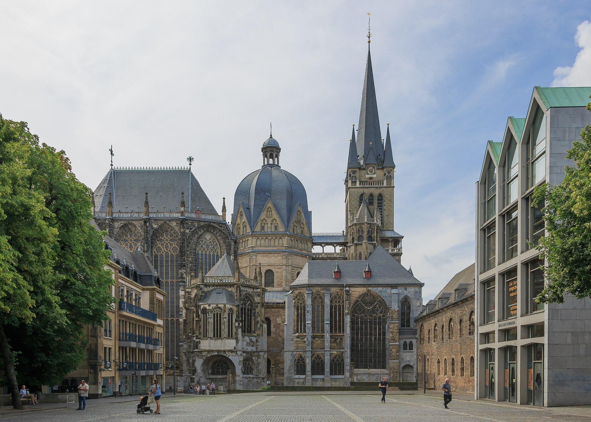 Von einem umbauten gepflasterten Platz aus sieht man den schlanken gotischen Turm, die Kuppel des achteckigen ursprünglichen Kirchenraums und das gotische Schiff des Aachener Doms.