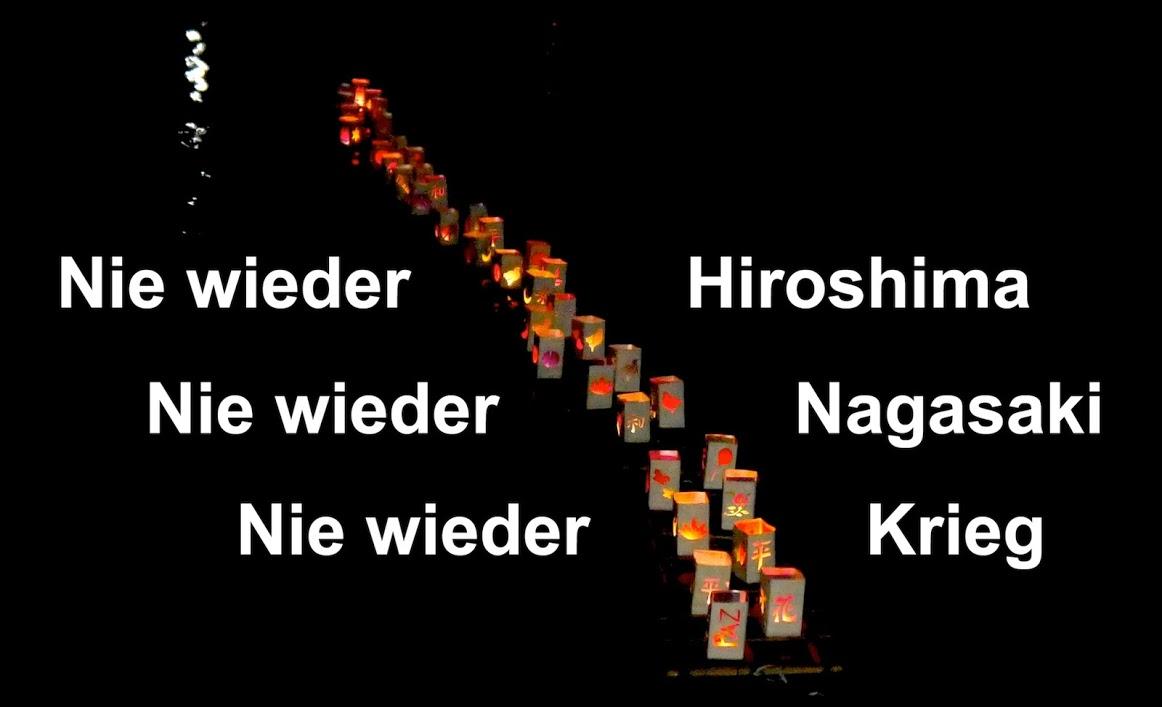 """Auf fast schwarzem, leicht reflektierendem Wasser treibt eine lockere Doppelreihe von weißen Papierlaternchen mit ausgeschnittenen Muster, durch die rötlich die brennenden Kerzen schimmern. Links und rechts daneben steht mit weißer Schrift """"Nie wieder Hiroshima. Nie wieder Nagasaki. Nie wieder Krieg."""""""