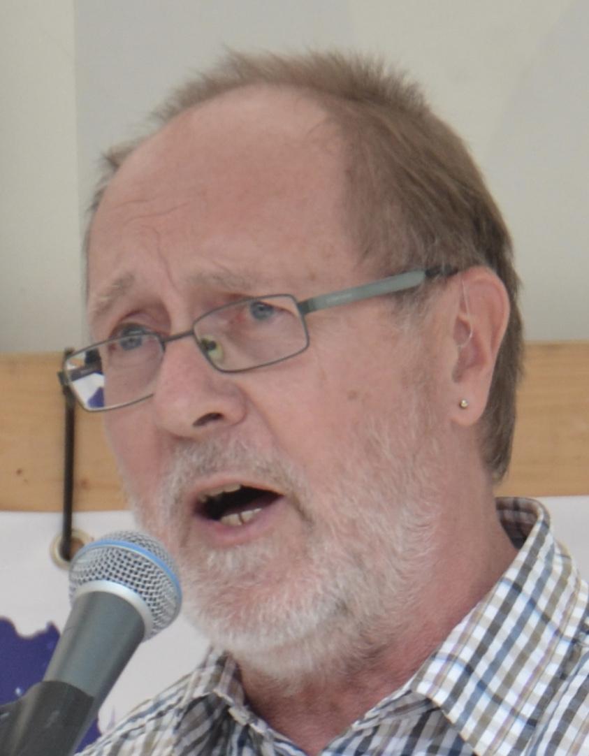 Ein älterer Herr mit hellen schütteren Haaren, Brille und grauem Bart spricht in ein Mikro.