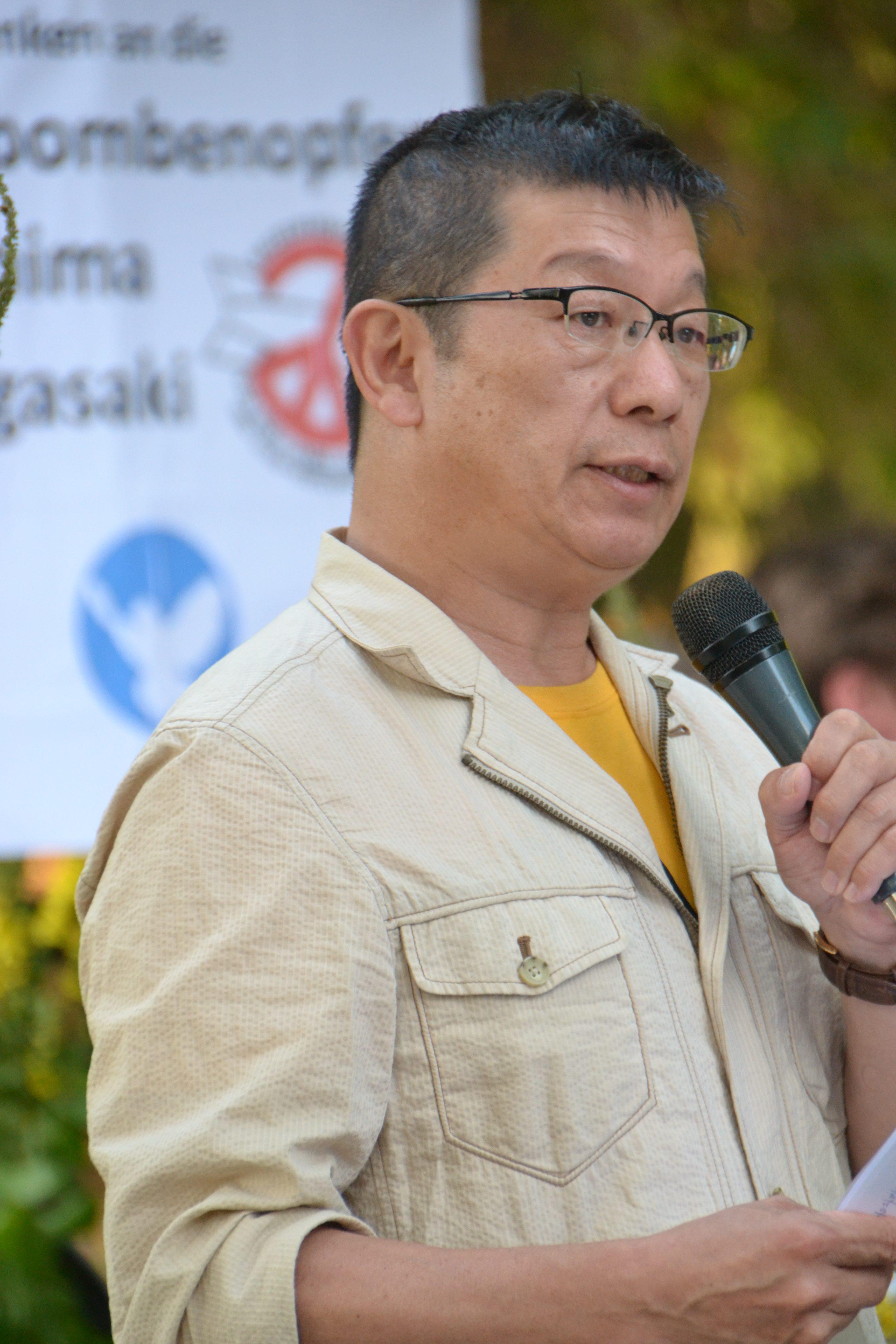 Ein asiatisch aussehender Herr mit kurzen schwarzen Haaren und Brille, in einem beigefarbenen Leinenhemd und sonnengelbem T-Shirt darunter spricht in ein Mikrophon. Im Hintergrund ein Schild mit einer Friedenstaube und dem Logo von ICAN, der Internationalen Kampagne zur Abschaffung der Kernwaffen.