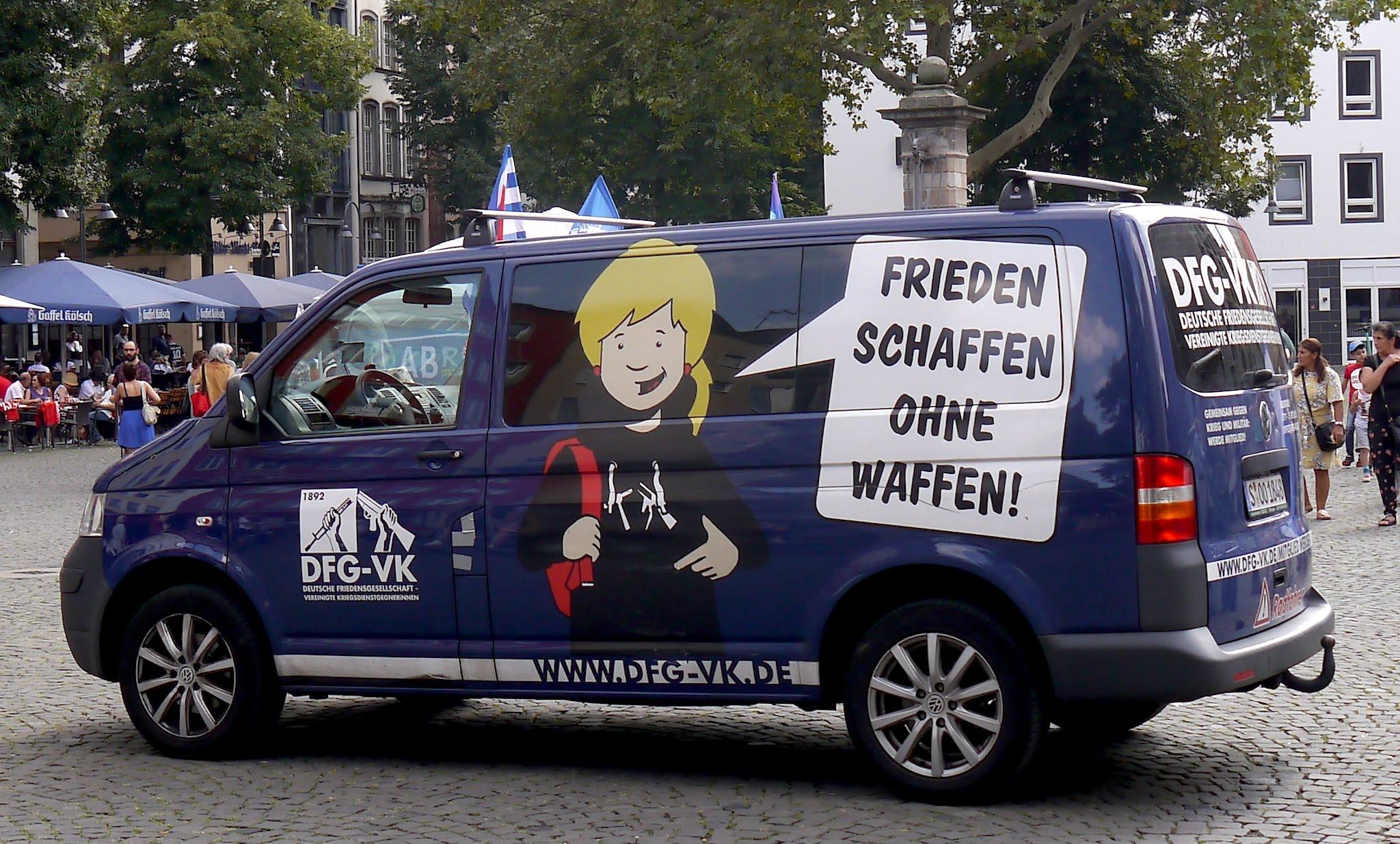 Ein dunkelblauer VW-Transporter mit einer Comic-Figur, die einen Schüler darstellt.