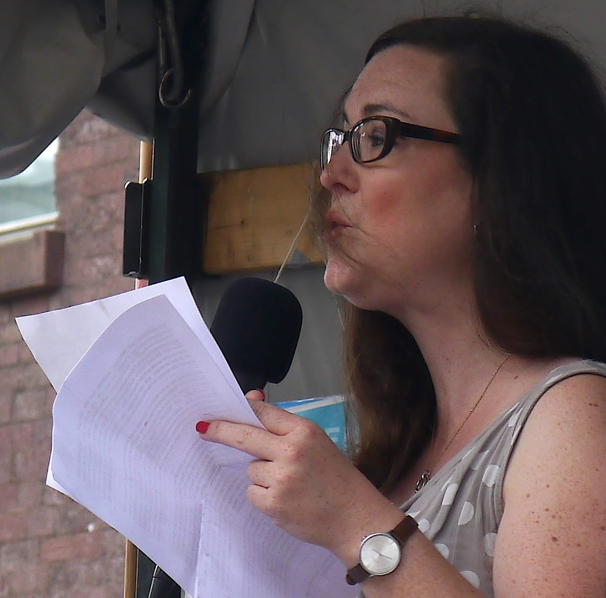 Eine junge Frau mit dunklen, langen Haaren, dunkler Brille in ärmellosem Sommerkleid hält weißes Papier in der Hand und spricht in ein Mikrophon.
