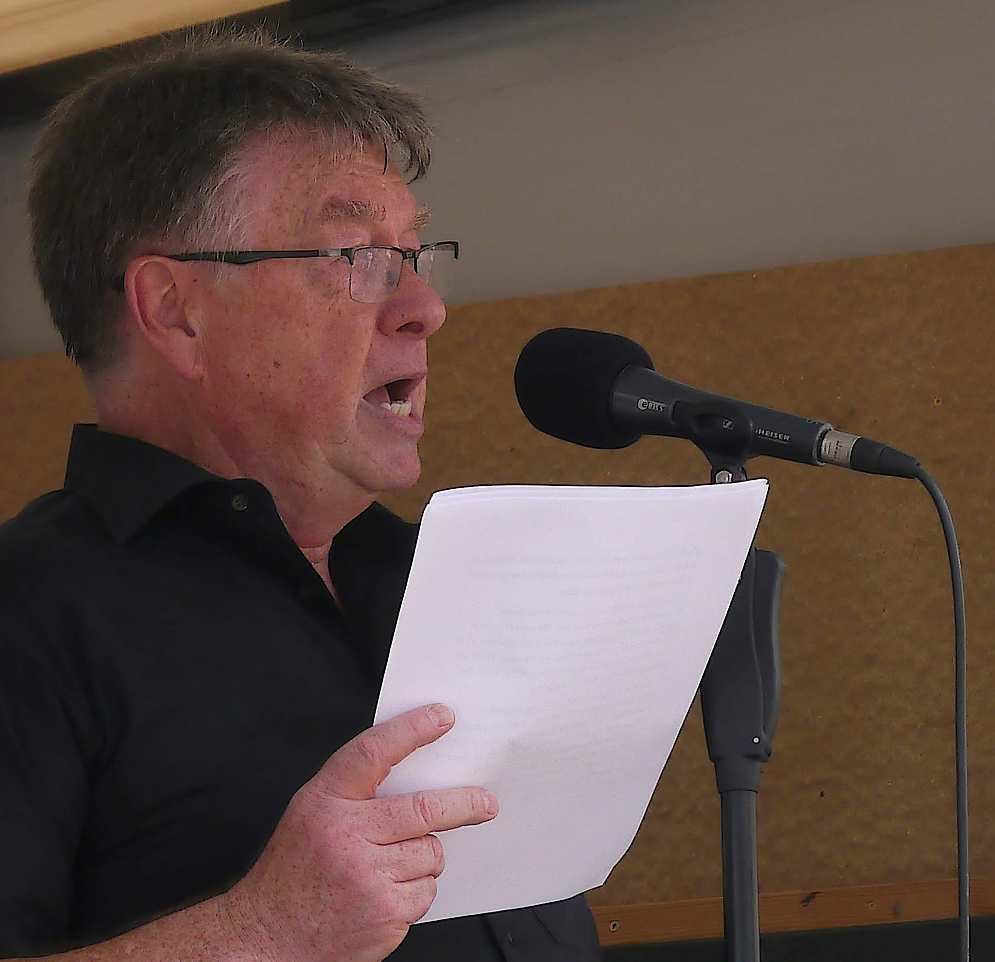 Ein älterer Herr mit kurzen, dunklen haaren und Brille, der ein Blatt Papier in der Hand hält, spricht in ein Mikro.