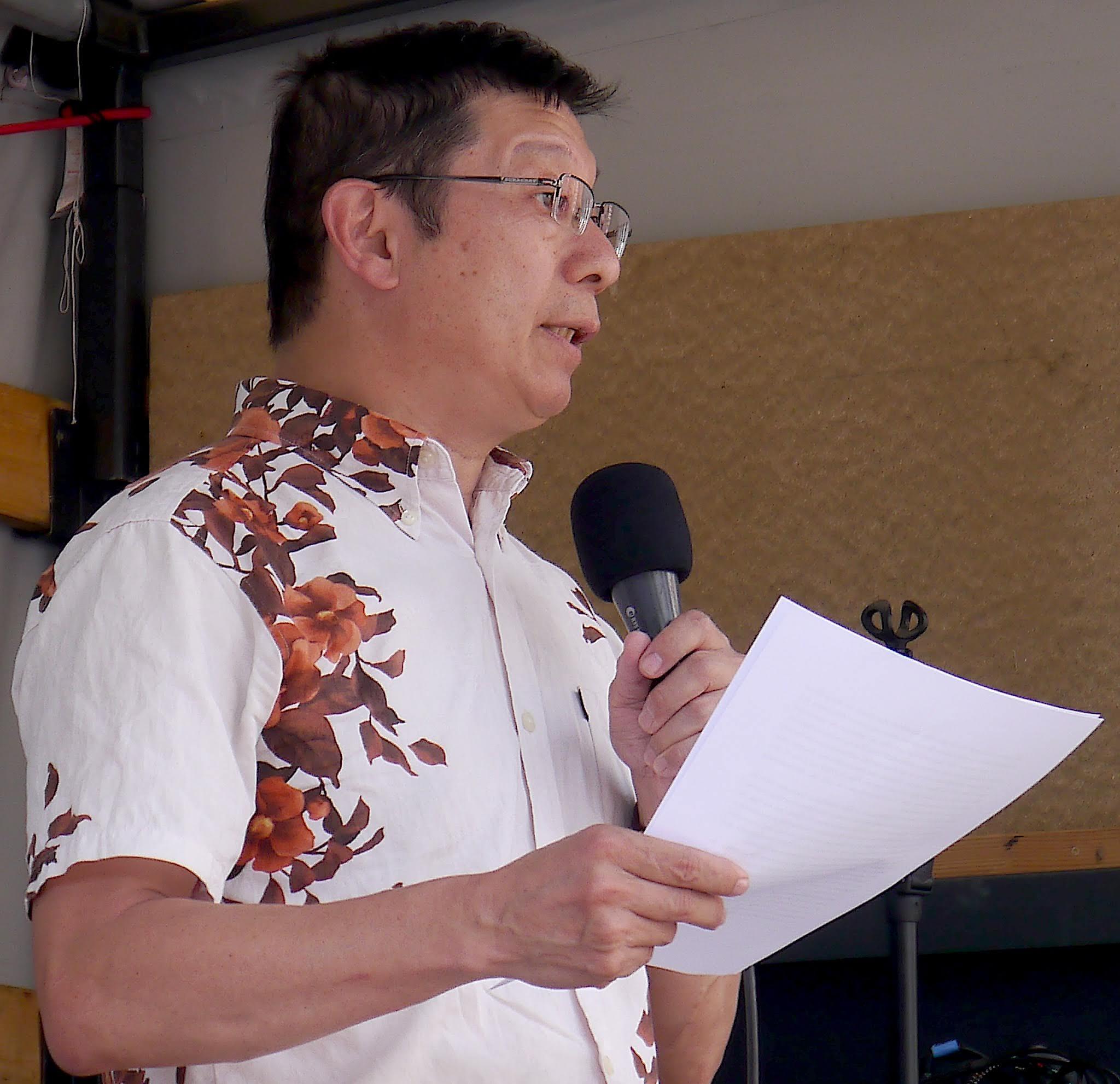 Ein ernster Mann mit dichten, schwarzen kurzen Haaren und Brille, der ein Blatt Papier in der Hand hält und ein kurzärmliges weißes Hemd mit Blumenverzierungen trägt, spricht in ein Mikro.
