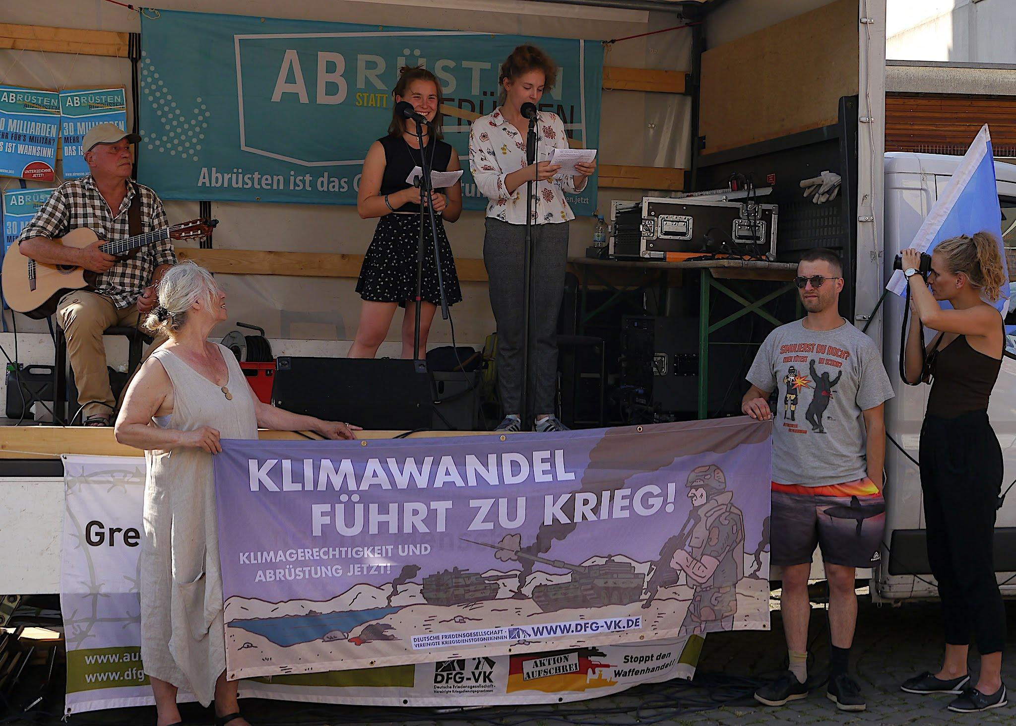 """Auf der kleinen Bühne stehen zwei junge Mädchen. Dahinter ein türkisfarbenes Transparent """"Abrüsten statt aufrüsten"""""""