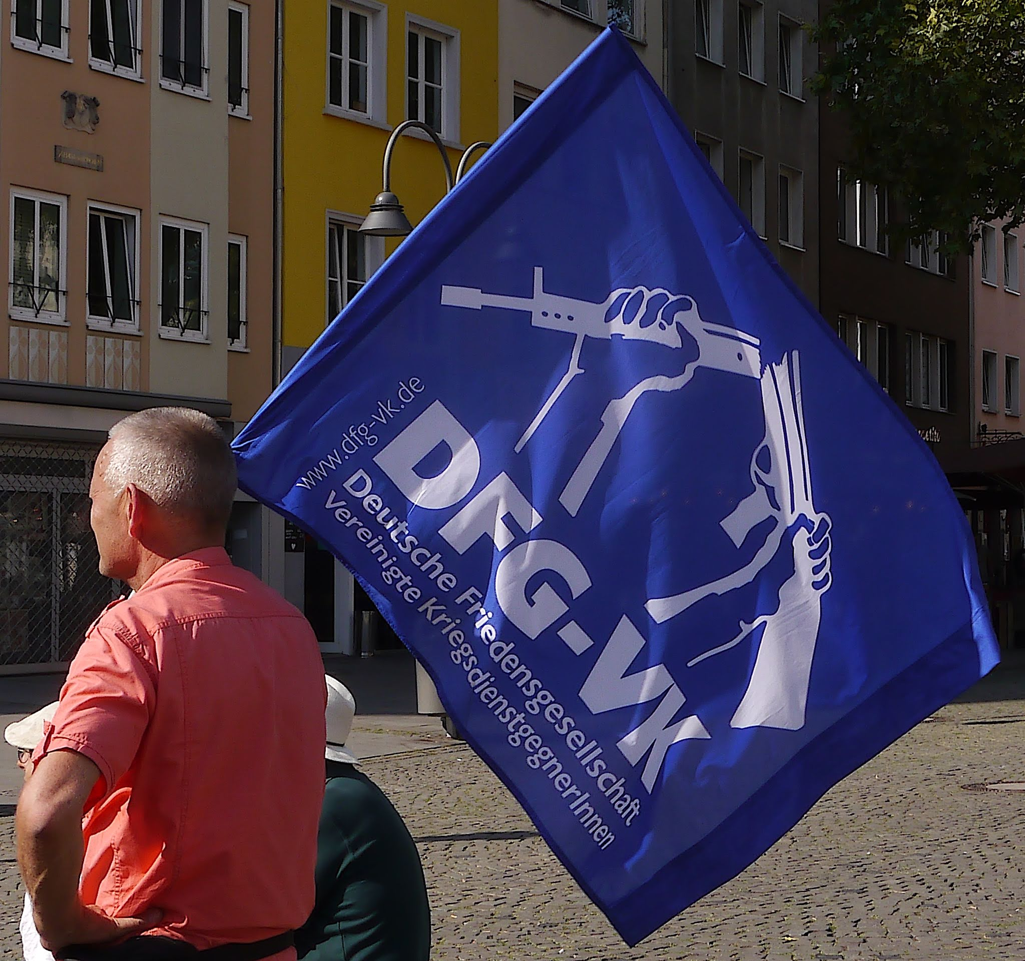 """Ein Mann in rötlichem Hemd mit grauweißen Haaren trägt eine blaue Flagge, auf der """"DFG-VK"""" und zwei Hände, die ein Gewehr zerbrechen zu sehen sind."""