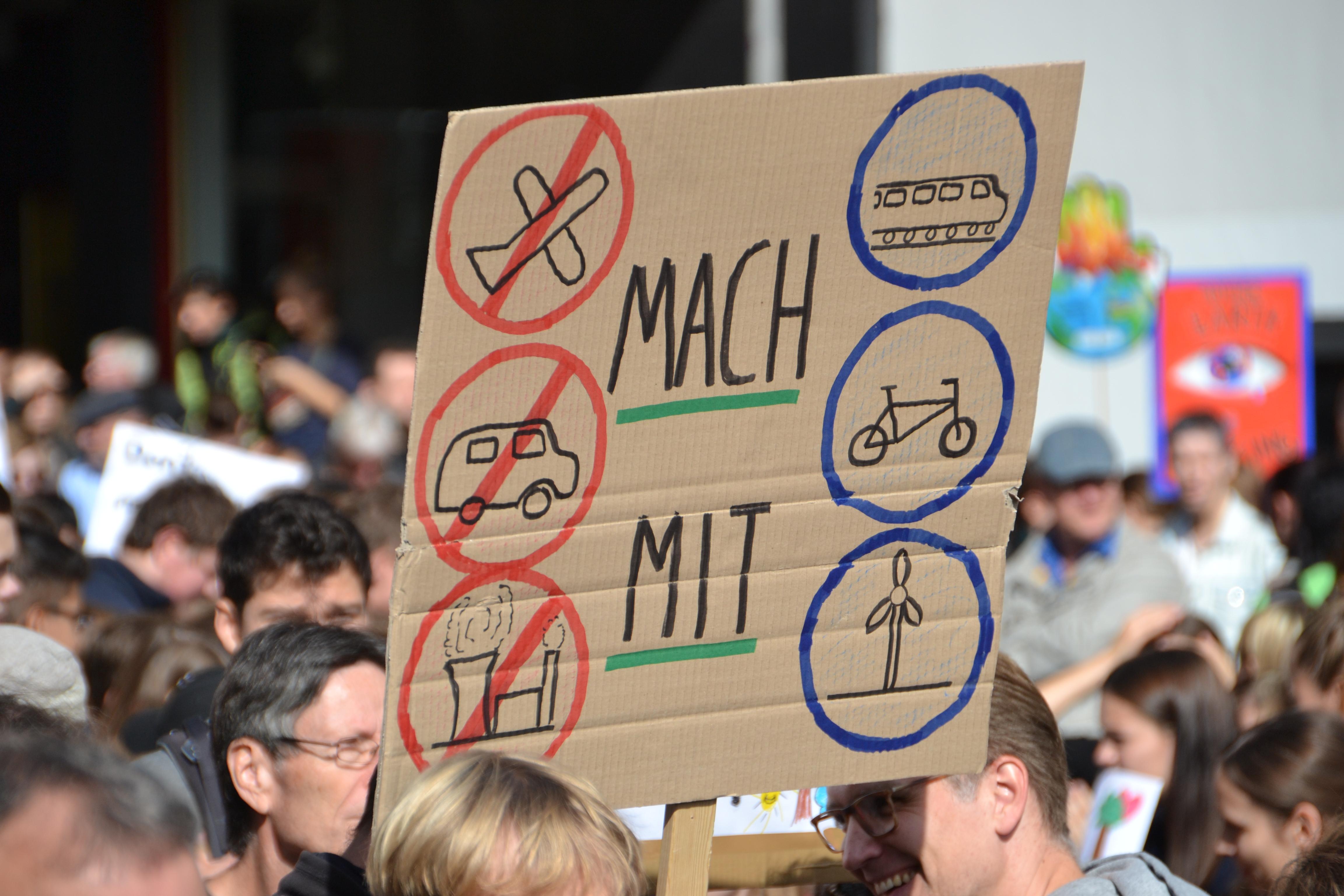 Ein selbst gemaltes Pappschild mit angedeuteten Verbotsschildern für Flugzeug, Auto und Kohlekraftwerk und Gebotsschildern für Bahn, Fahrrad und Windkraftwerk.