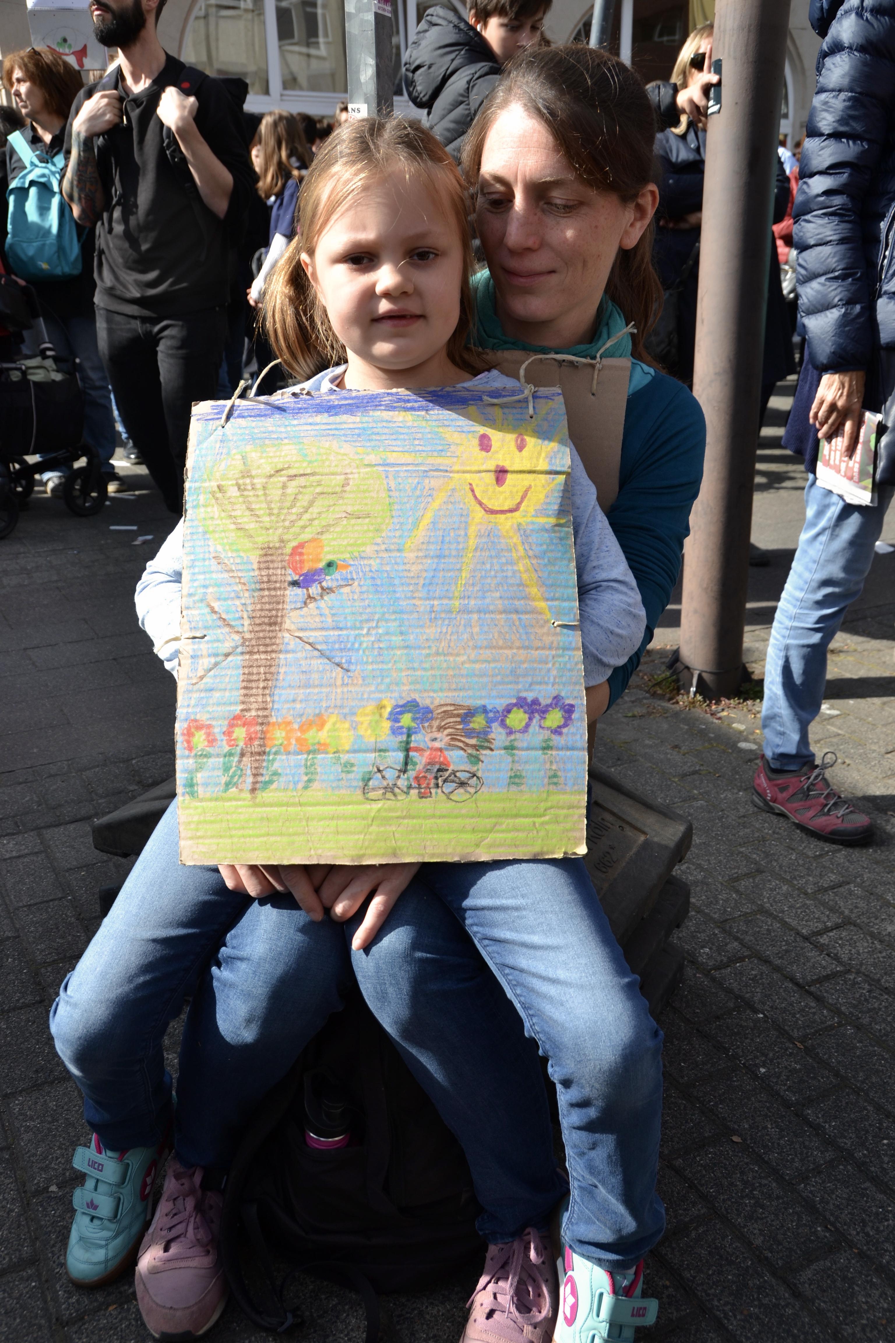 Ein Mädchen zeigt ihr auf Pappe gemaltes Bild mit einem Baum, einer freundlichen Sonne, Blumen und Schmetterlingen. Es sitzt auf dem Schoß seiner Mutter, die in der Sonne zwischen umherlaufenden Menschen auf einem Hocker sitzt.
