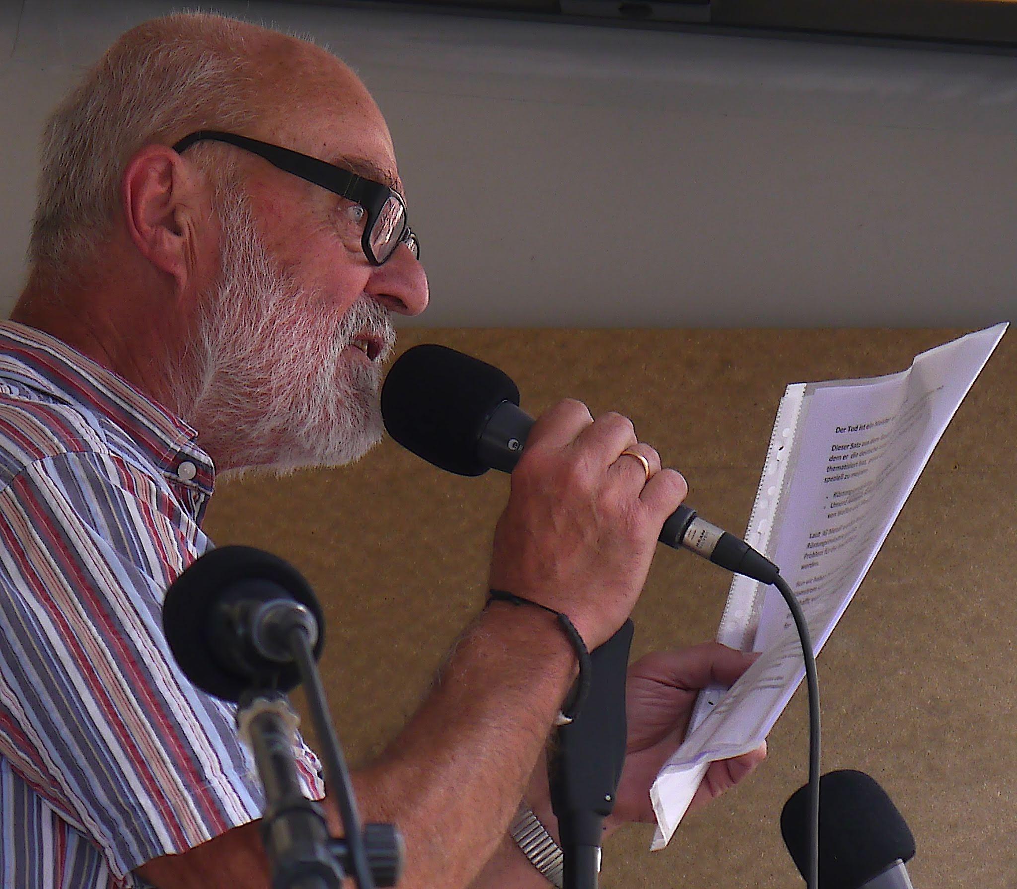 Ein älterer kräftiger mann mit kurzrasierten grauen Haaren, einem kurzen grauen Bart und mit dunkler Hornbrille spricht in ein Mikro.