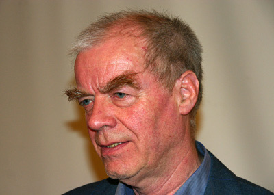 Kopfporträt eines mittelalten Mannes mit kurzen, schütteren, nach vorn gebürsteten Haaren und buschigen dunklen Augenbrauen.
