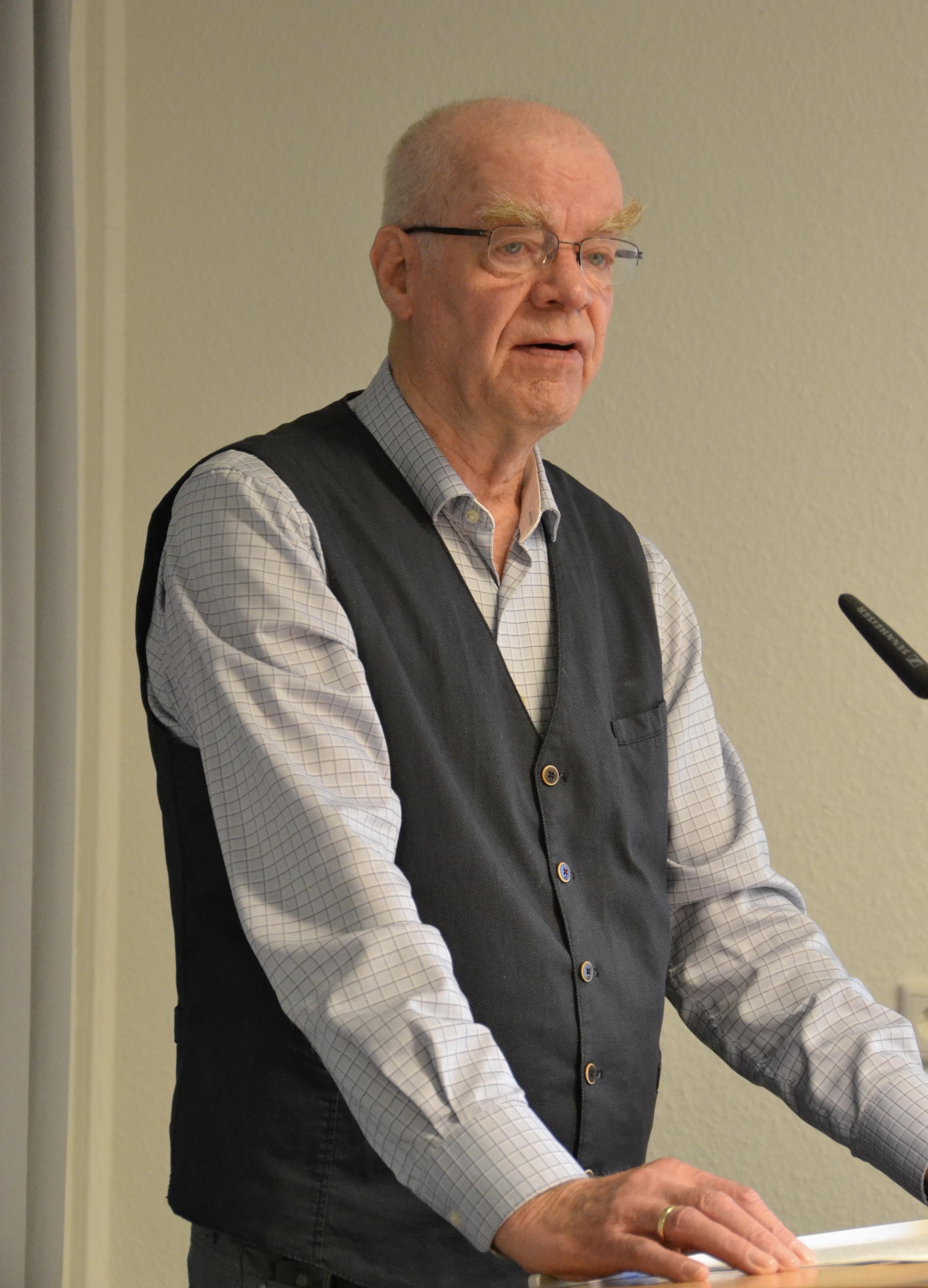 Ein großer älterer Herr mit weißen kurzgeschorenen Haaren und Brille, der ein helles Hemd und eine dunkle Weste darüber trägt, spricht in ein Mikro.
