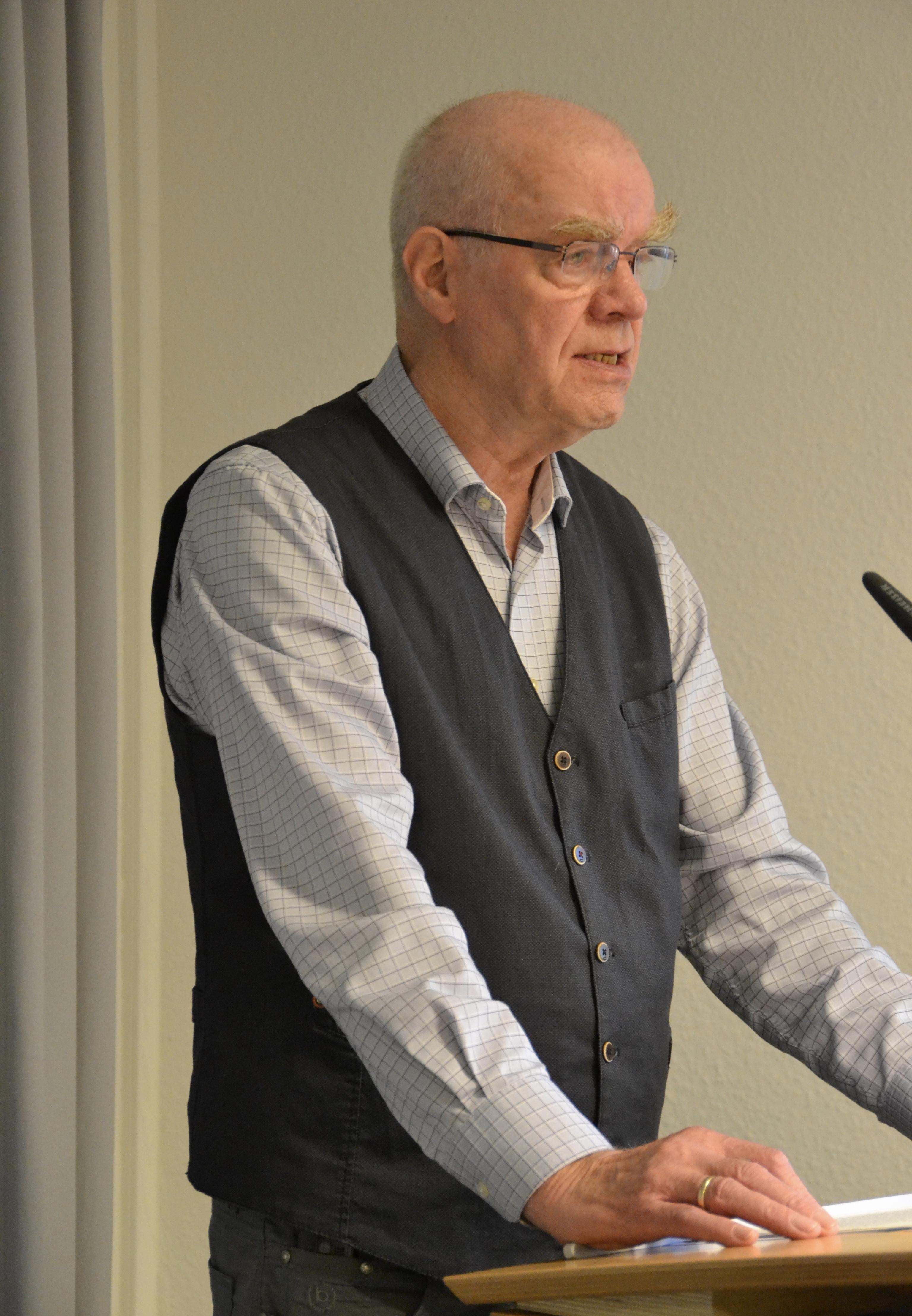 Ein großer älterer Herr mit einem Rest grauer kurzgeschorener Haare, buschigen rötlich-grauen Augenbrauen und Brille, der ein helles Hemd und eine dunkle Weste darüber trägt, spricht in ein Mikro.