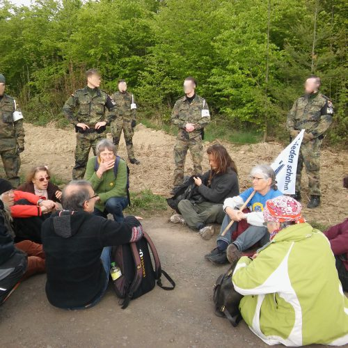 Im Vordergrund sitzen einige Männer und Frauen auf einem asphaltierten Weg. Dahinter, auf einem trockenen Grasstreifen stehen bewaffnete, uniformierte Soldaten, die sie bewachen. Im Hintergrund ist Wald.