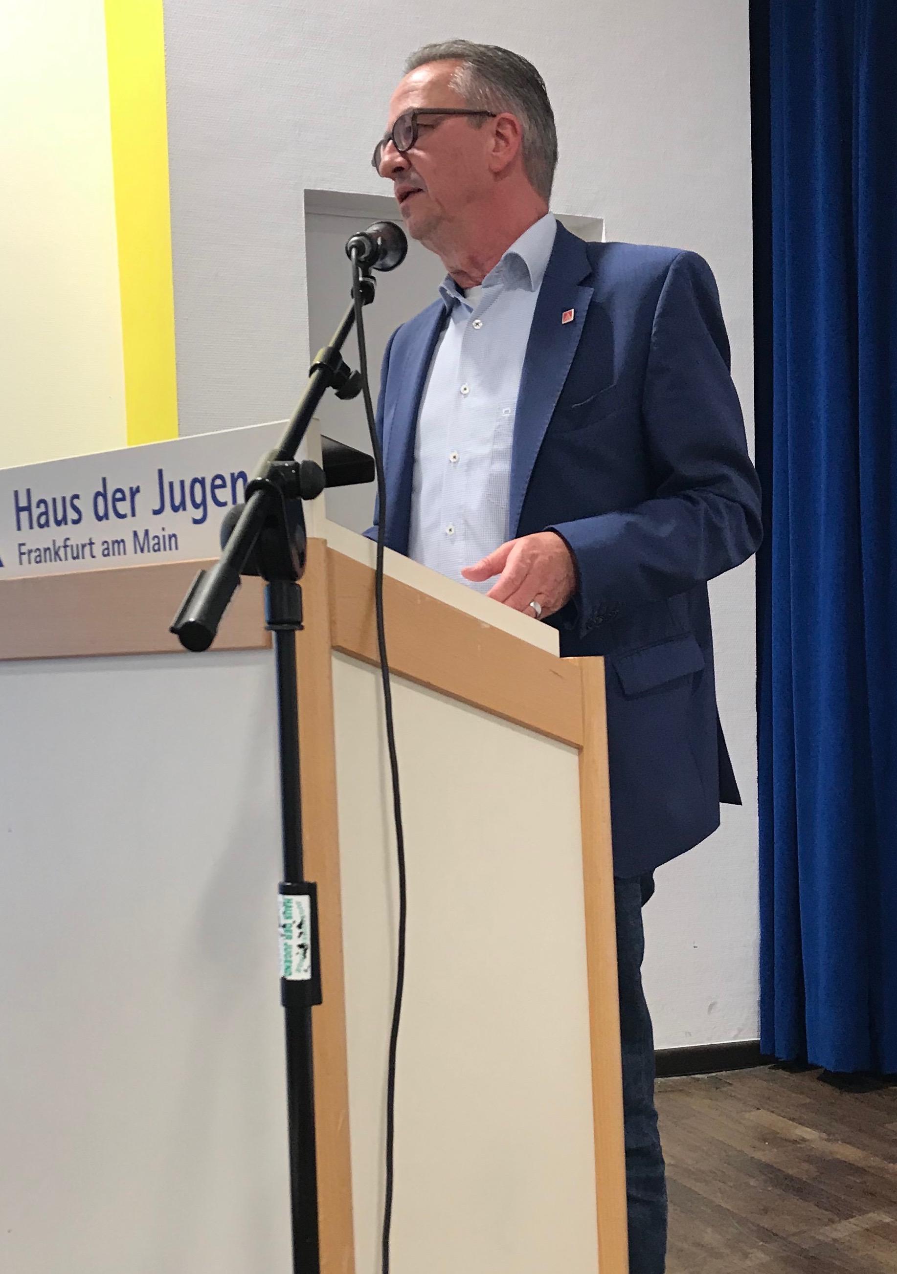 Ein mittelalter Herr in dunklem Anzug, weißem Hemd steht hinter einem hellen Rednerpult und spricht in ein Mikro.