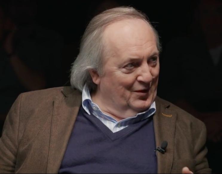 Ein älterer Herr mit Glatze und einem grauen Haarkranz in braunem Jackett, hellem Hemd und lila Pullover schaut im Gespräch leicht nach rechts.