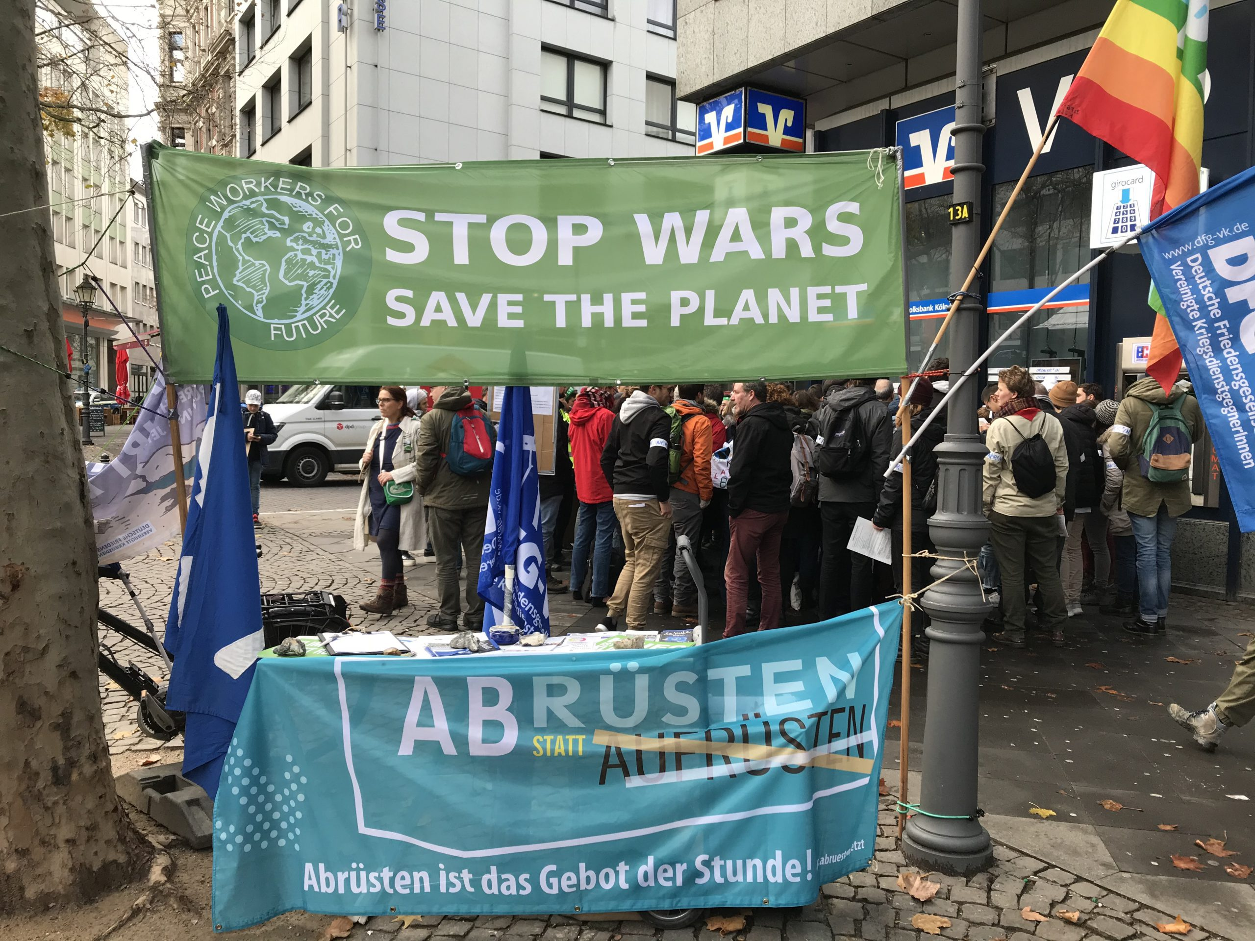 """Infostand mit zwei Transparenten """"Stop wars - save the planet"""" und """"Abrüsten statt aufrüsten"""""""