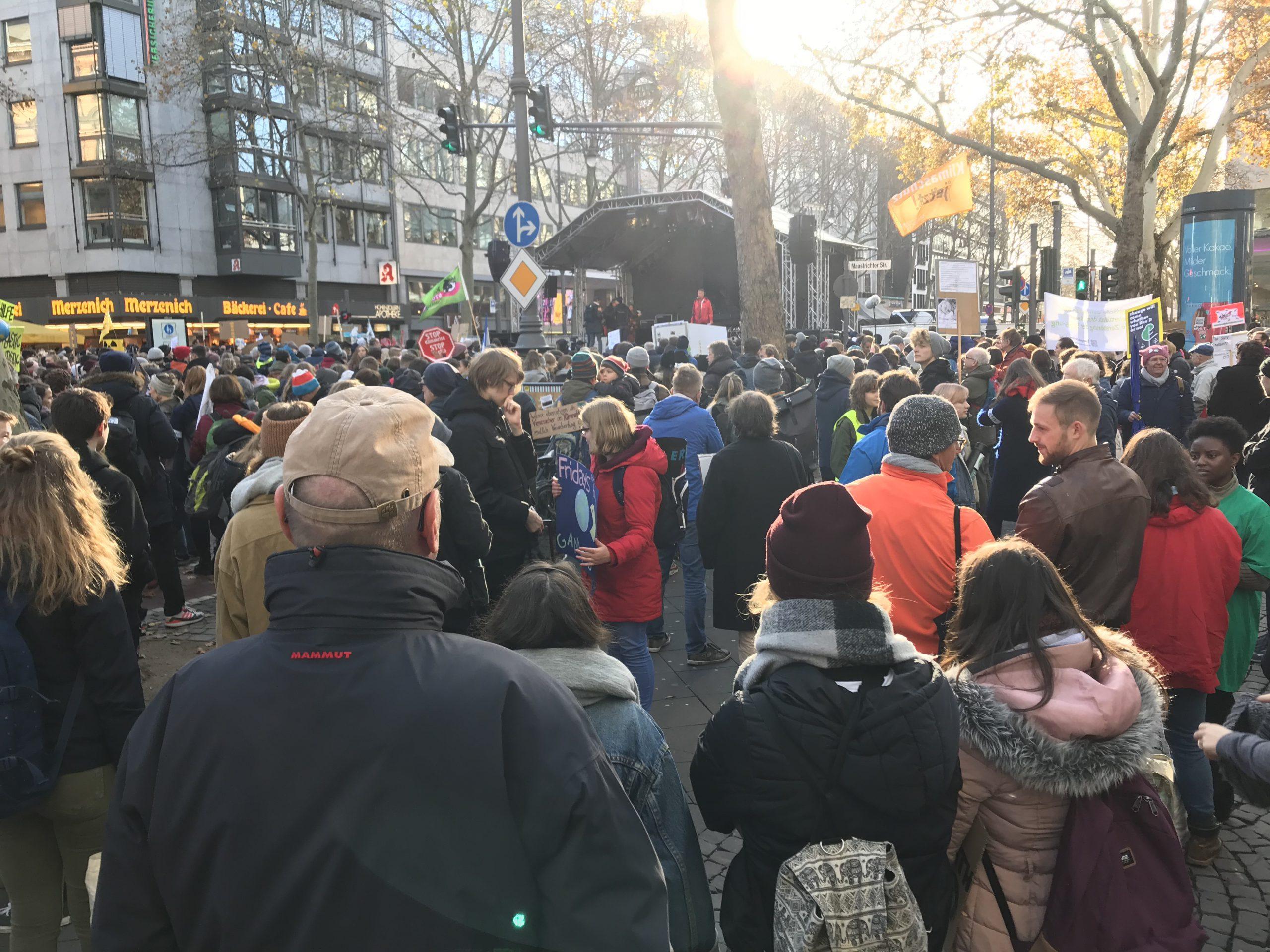 Im Gegenlicht ist im Bildhintergrund eine große Bühne zu sehen, auf der eine Person in roter Jacke steht. Vorn viele Leute in Winterkleidung, die zur Bühne schauen.