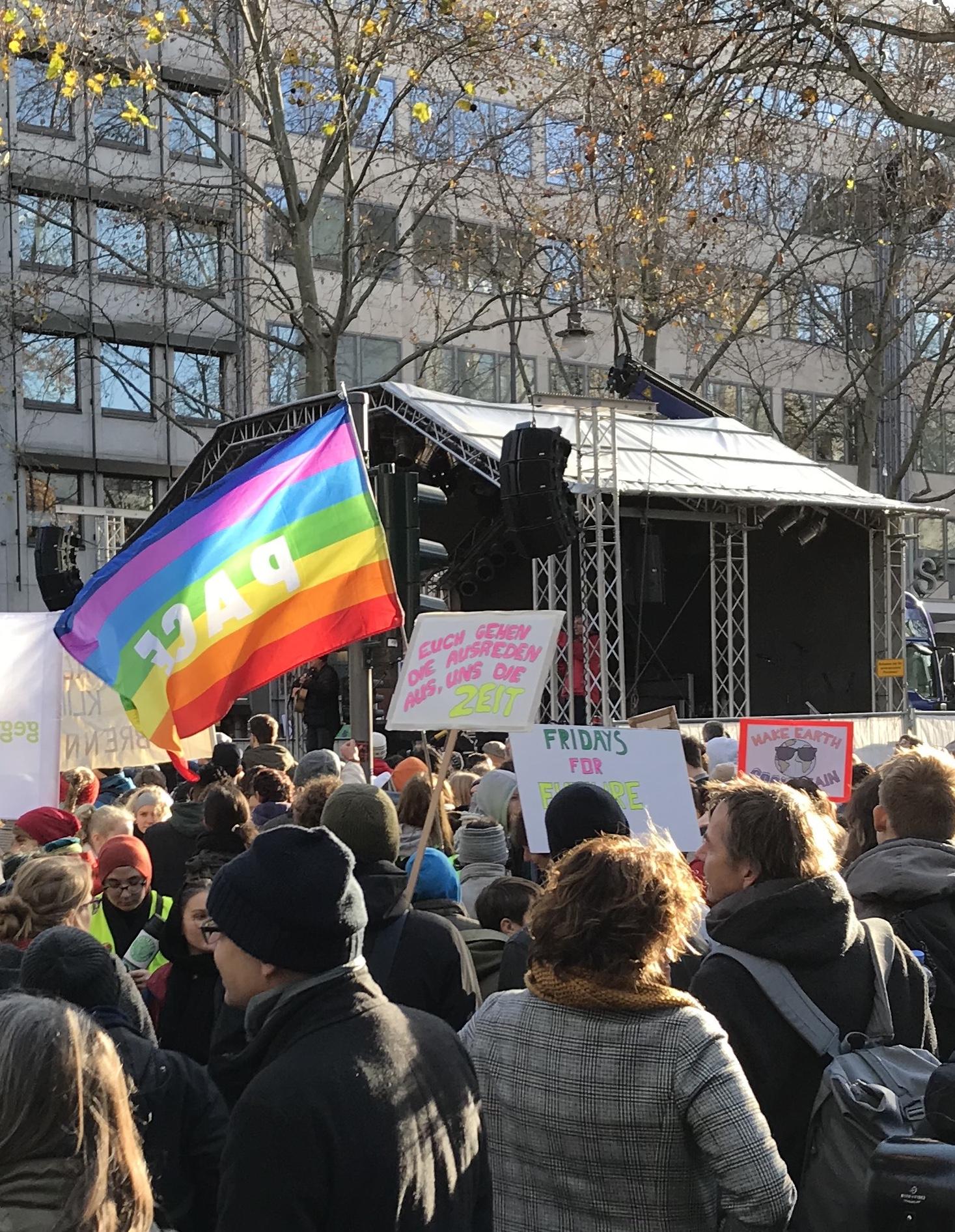 Ein Schild und eine Fahne mit Aufschriften verdecken den Blick auf die Bühne.