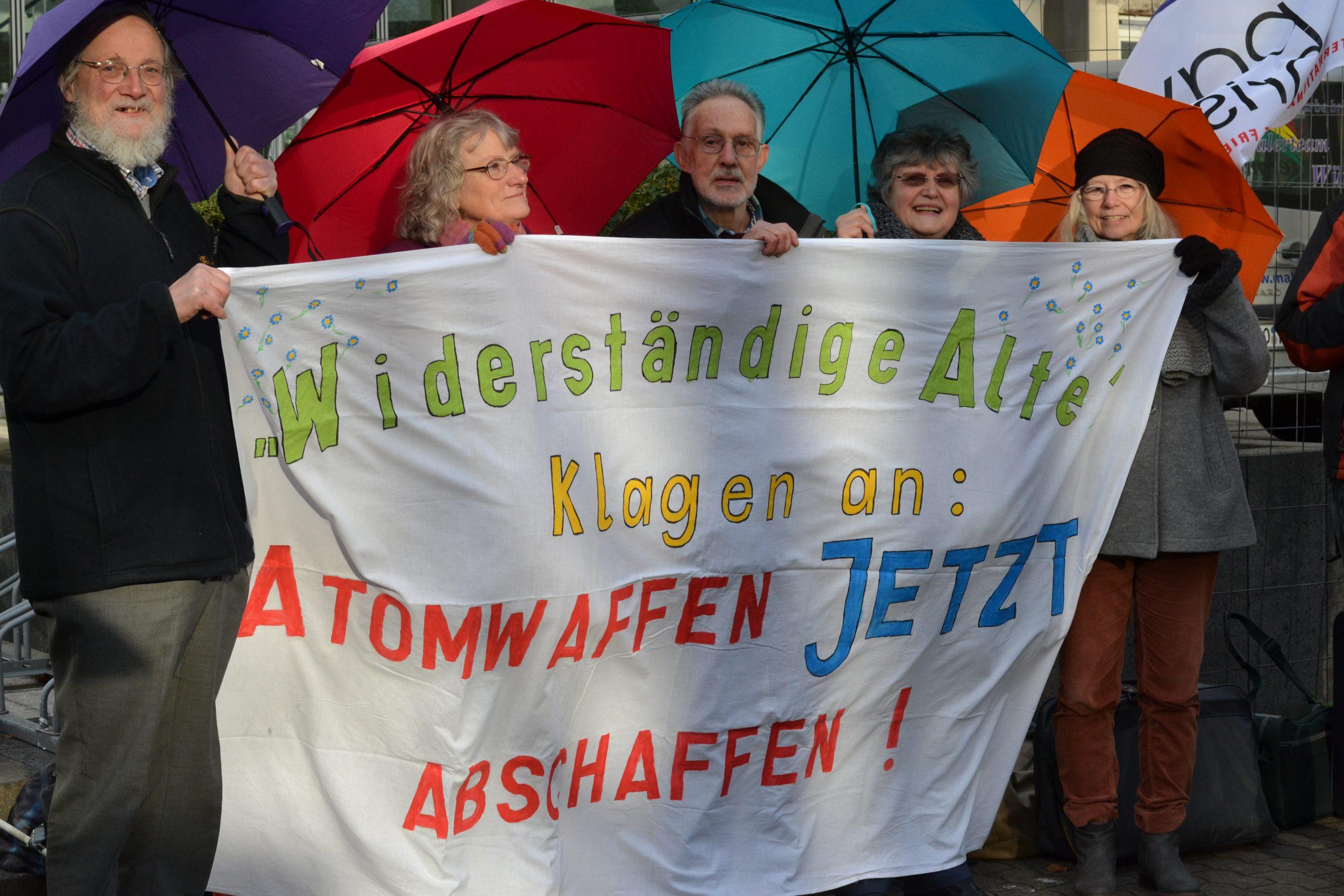 """Fünf ältere Menschen halten jeweils einen bunten Regenschirm hinter sich, während sie gemeinsam ein großes weißes Tuchtransparent tragen, auf dem mit bunten Farben steht """"Widerständige Alte klagen an: ATOMWAFFEN JETZT ABSCHAFFEN!"""