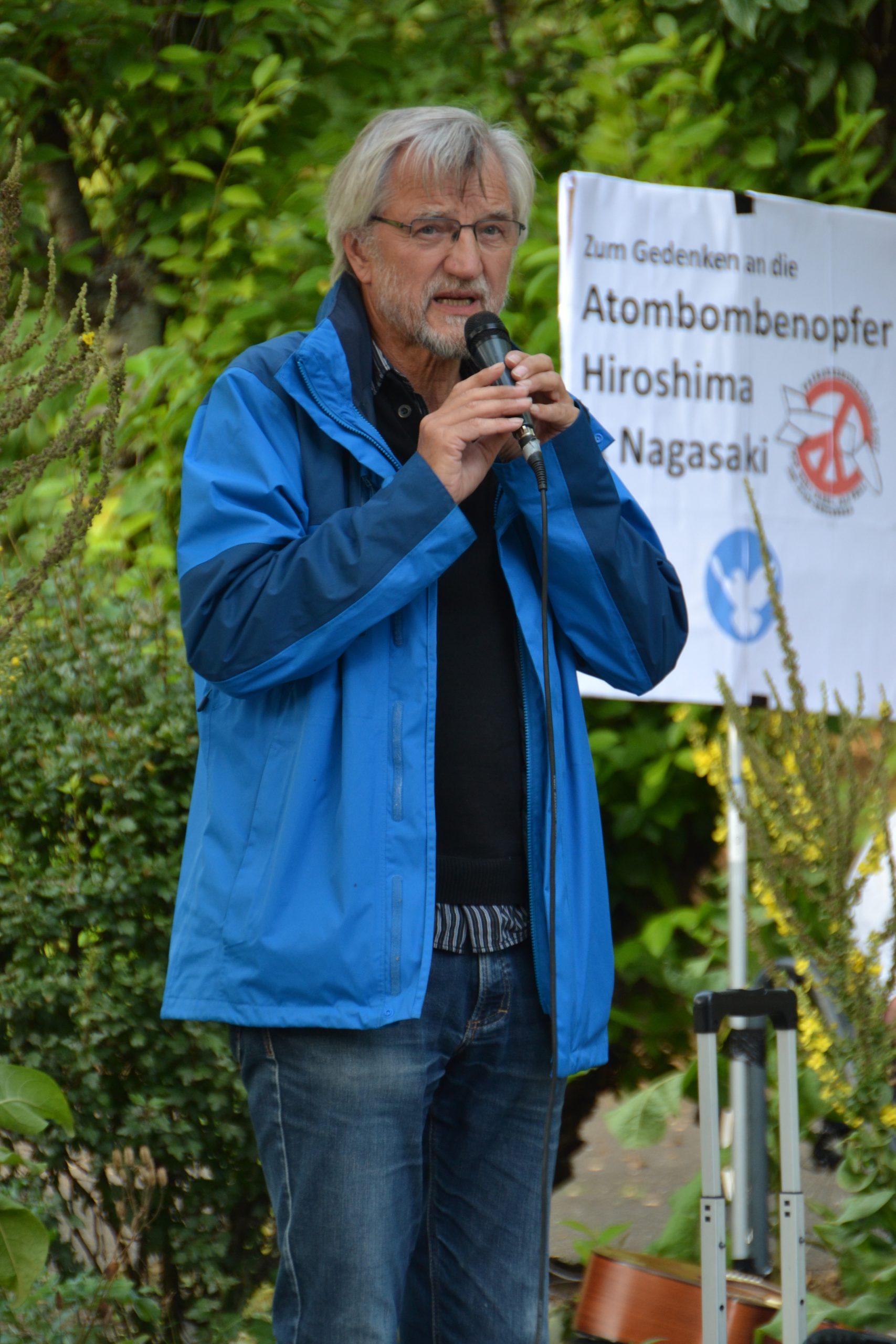 """Ein schlanker älterer Herr in blauer sportlicher Jacke und Jeans spricht in ein Mikro. Im Hintergrund ein Transparent mit der Aufschrift """"Zum Gedenken an die Atombombenopfer"""", """"Hiroshima"""", """"Nagasaki"""""""