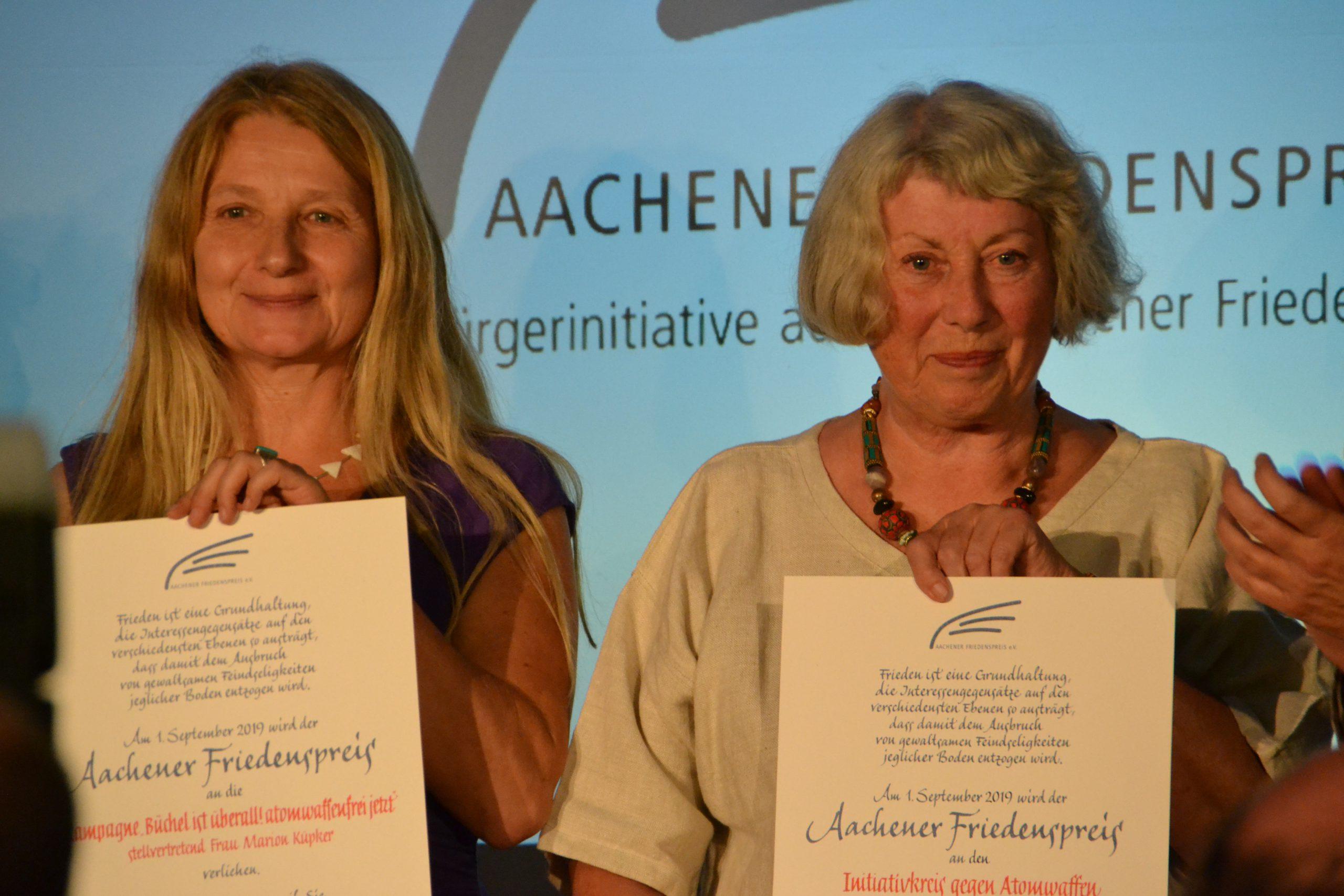Zwei glücklich strahlende ältere Frauen halten jeweils eine Urkunde vor sich.