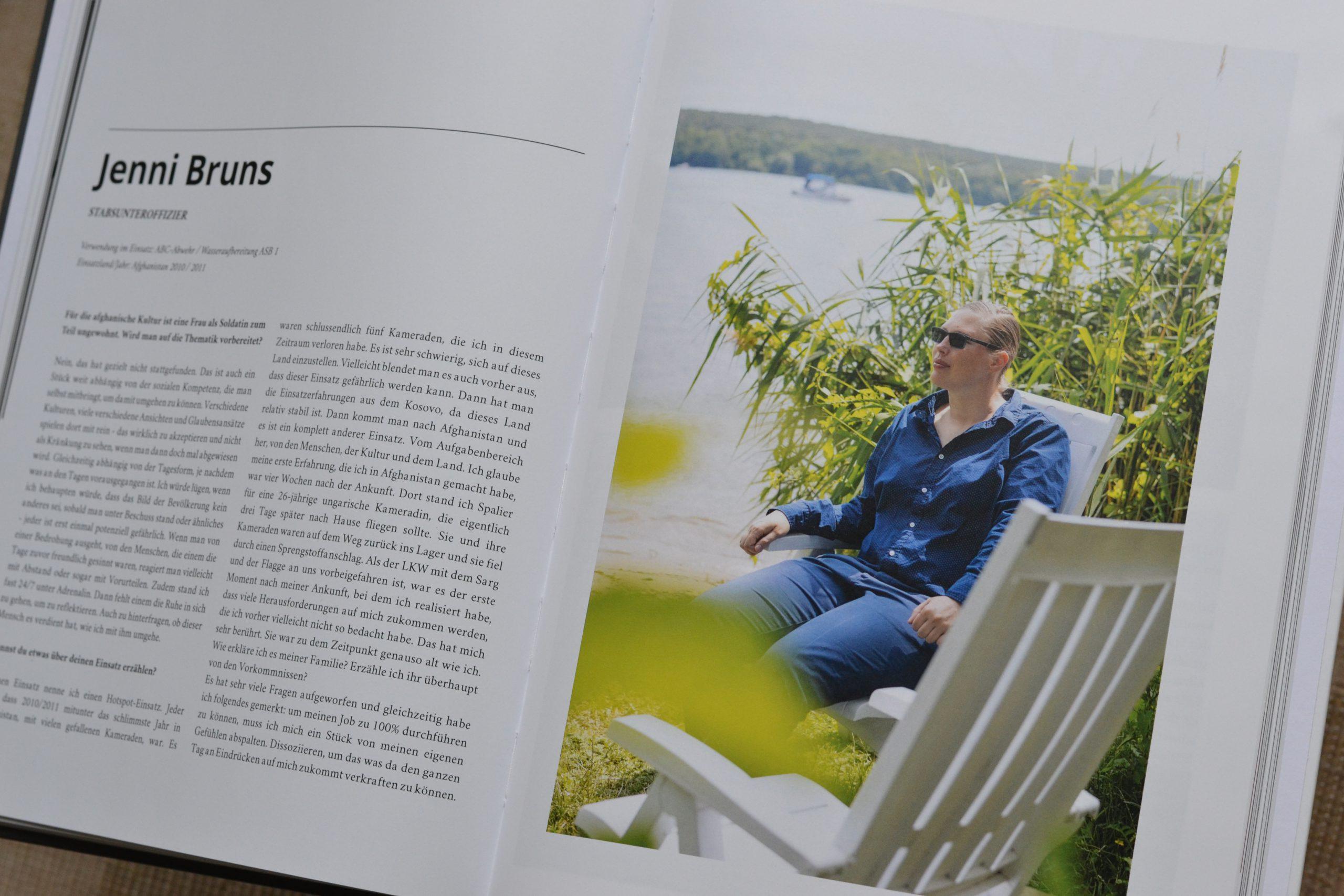 Ein aufgeschlagenes Buch zeigt rechts eine Frau mit Sonnenbrille in blauer Bluse und Jeans, die an einem sonnigen Tag auf einem weißen Gartenstuhl vor einem See sitzt. Links ist ihr Name - Jenni Bruns - und viel Text gedruckt.