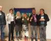 """Drei Männer und drei Frauen unterschiedlichen Alters strahlen mit Sektgläsern in den Händen in die Kamera. Im Hintergrund eine an der Wand aufgehängte Regenbogenflagge mit der Aufschrift """"pace"""" , die allerdings nur teilweise zu sehen ist."""