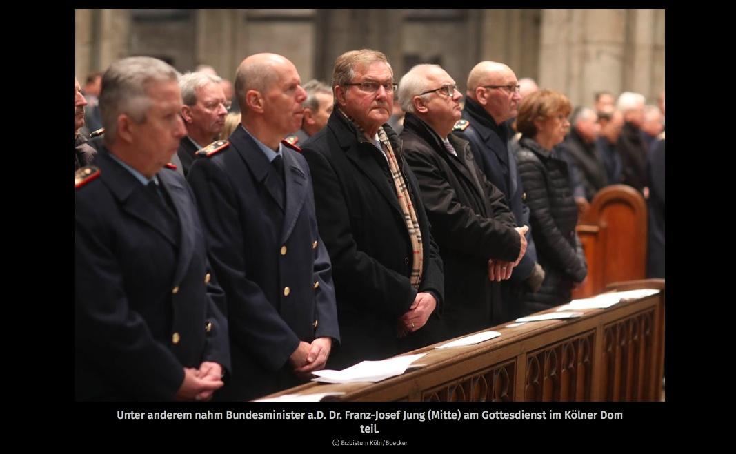 Die erste Reihe im Kirchenschiff zeigt Herren in dunklen Uniformmänteln und Oberbürgermeisterin Reker, die zum Altar schauen. Nur ein Mann im dunklen Zivilanzug schaut nach rechts, direkt ins Objektiv der Kamera.