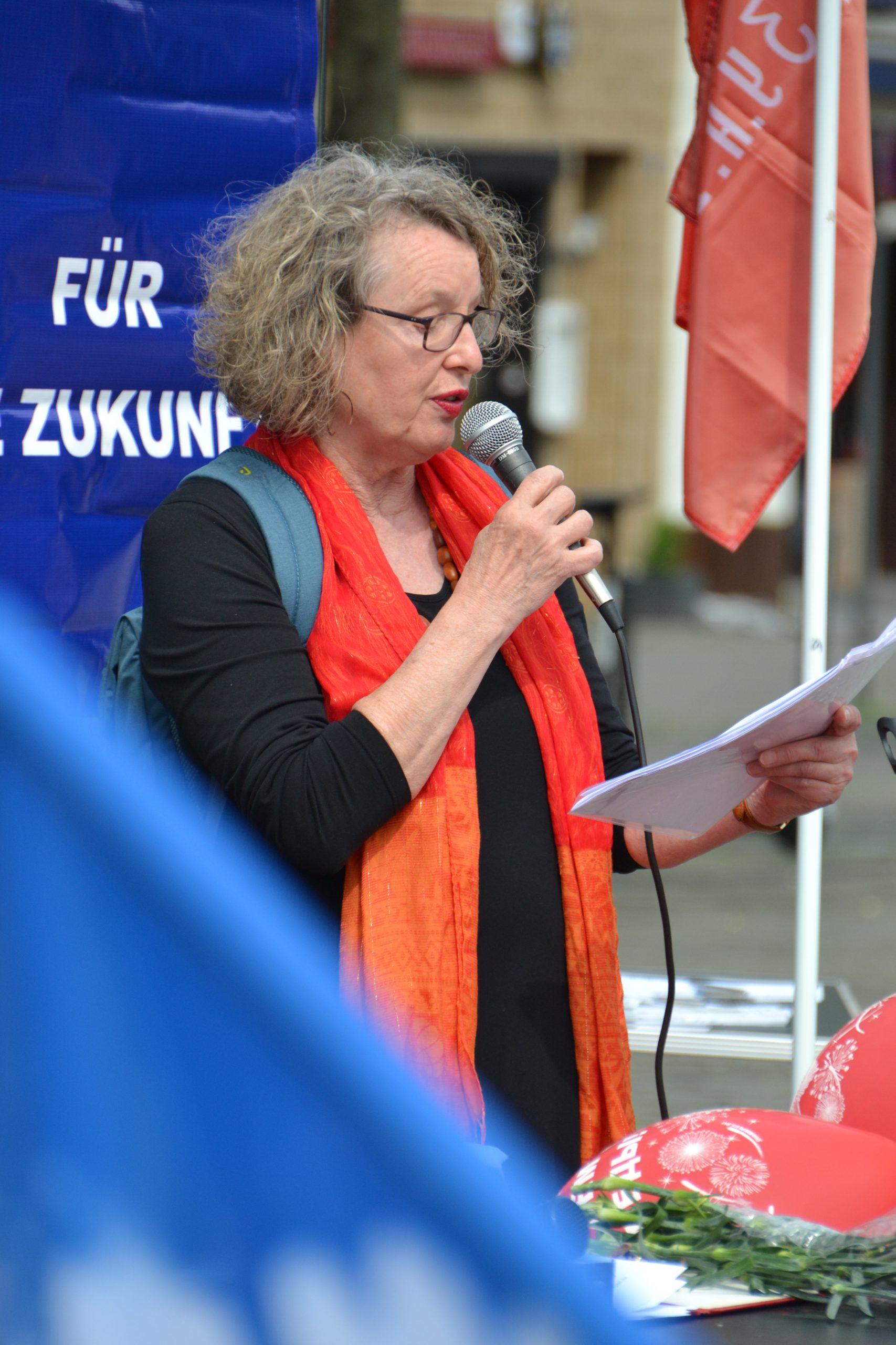 """Eine Frau mit Brille und dicken graumelierten kurzen Locken spricht in ein Mikro. Sie trägt ein schwarzes Oberteil und ein langes hellrotes Tuch. Hinter ihr ist das Fragment eines blauen Plakats mit der weißen Aufschrift """"Für Zukunft"""" zu sehen."""