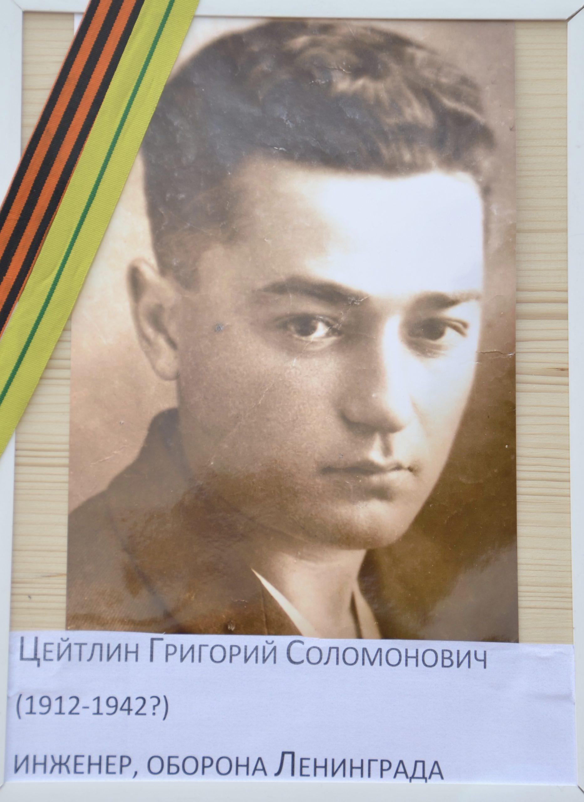 Ein auf Sperrholz geklebtes, braun-weißes Portraitfoto eines jungen Mannes mit dichtem, welligen Haar. Darunter die russischen Daten zur Person.