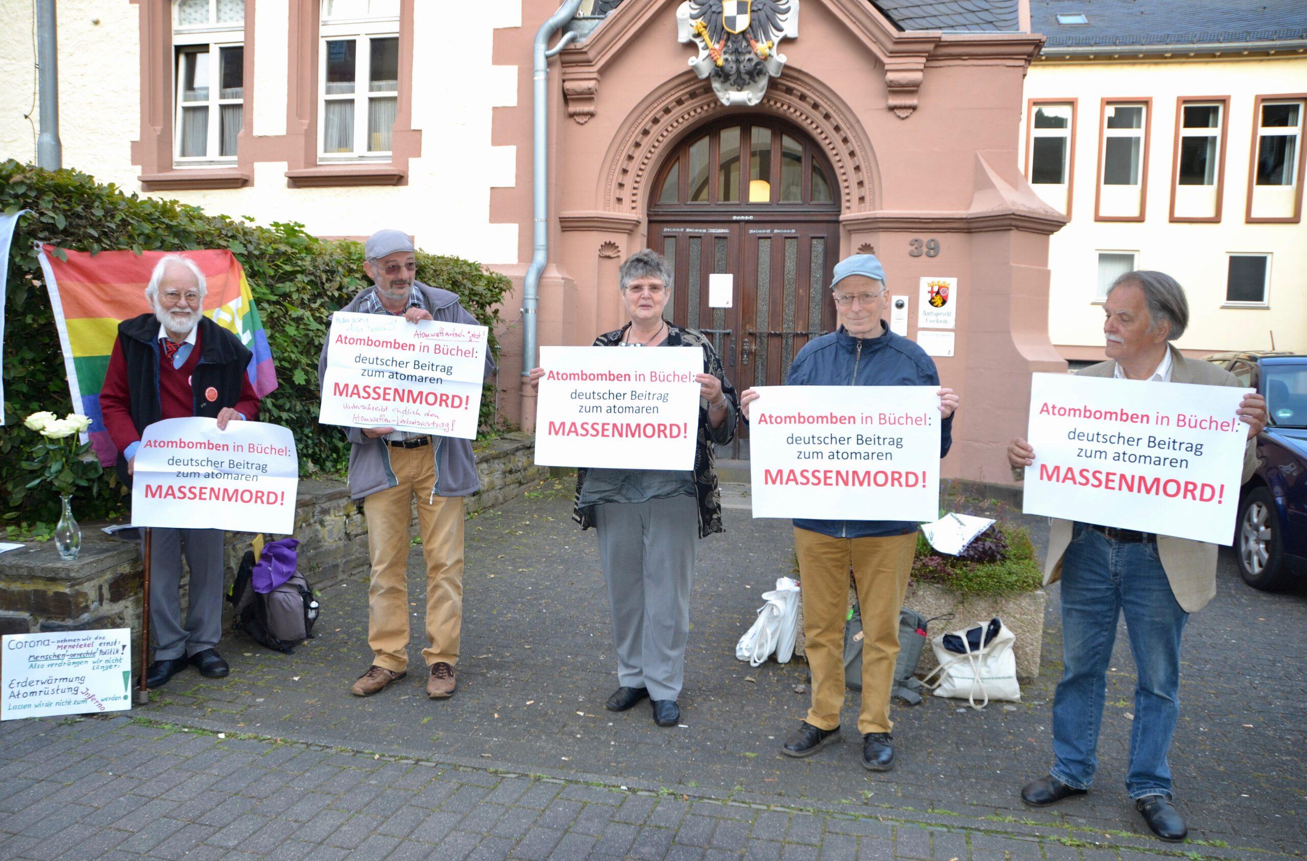 Fünf Männer und eine Frau stehen vor einem romantischen Eingangsportal aus rotem Sandstein und halten den Betrachter*innen jeweils ein weißes DIN A 3-formatiges Schild mit roter und schwarzer Schrift entgegen.
