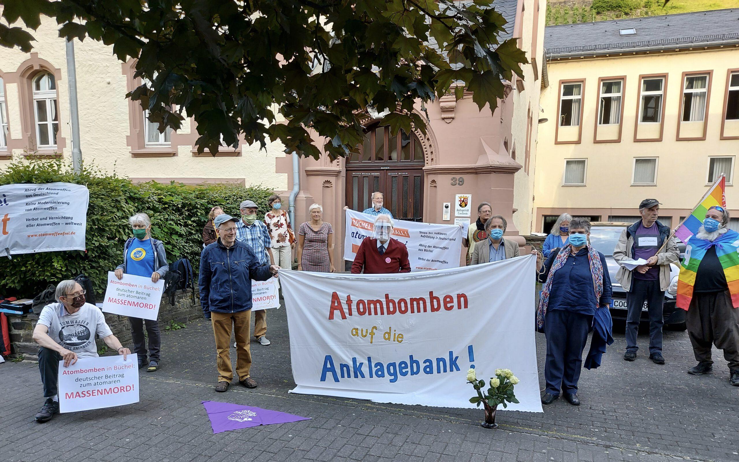 """Eine Gruppe Menschen mit Mundschutz steht verteilt hinter und neben einem Stoffbanner mit der Aufschrift """"Atombomben auf die Anklagebank!"""". Im Hintergrund ein Gebäude mit romantischem Natursteinportal."""