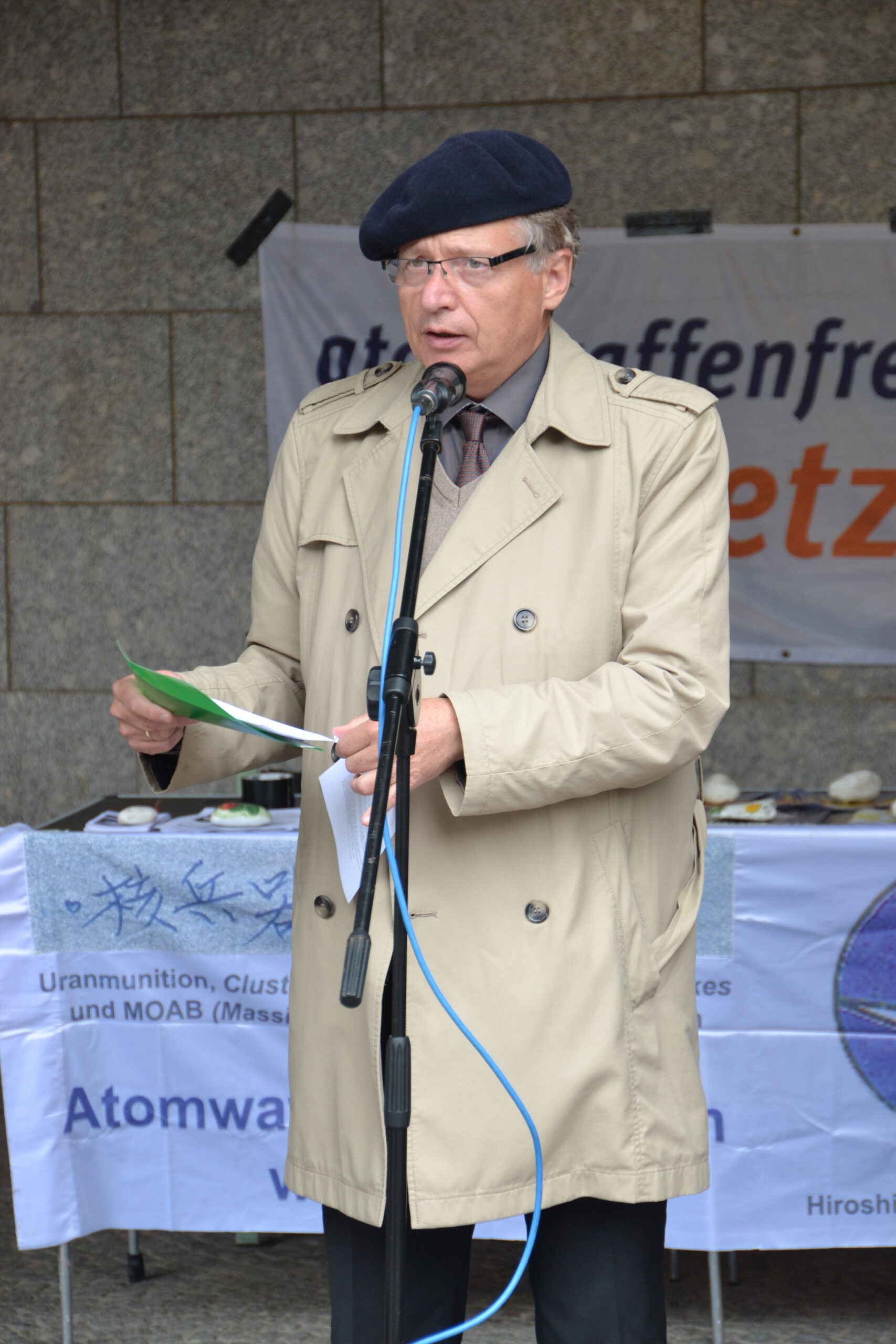 """Ein mittelalter Mann mit hellem Trenchcoat und schwarzer Mütze spricht in ein Mikro. Im Hintergrund ist ein Banner mit """"atomwaffenfrei Jetzt!"""" zu erkennen."""