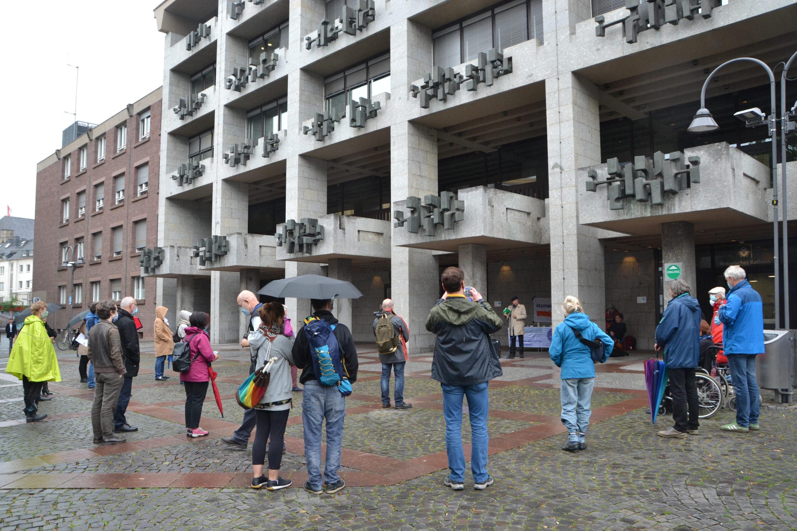 In lockerer Runde stehen etwa zwei Dutzend Leute zum Teil mit geöffneten Regenschirmen um einen Redner herum, der unter dem Fassadenvorsprung eines modernen Betongebäudes steht.