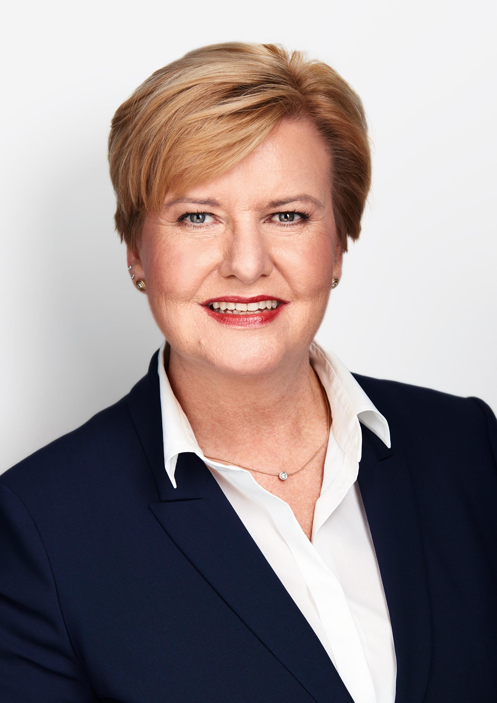 Schulterporträt einer energisch aussehenden Dame mittleren Alters mit kurzen auf der Seite gescheitelten blonden Haaren und professionell geschminktem Gesicht mit weißer Bluse und schwarzem Blazer.