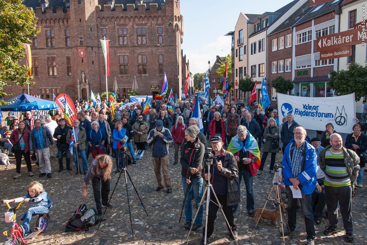 Eine Menge Leute mit Friedensfahnen, manche mit Kameras, stehen auf einem historischen Platz und schauen in Richtung Bühne, die sich links hinter dem Fotografen befinden muss.